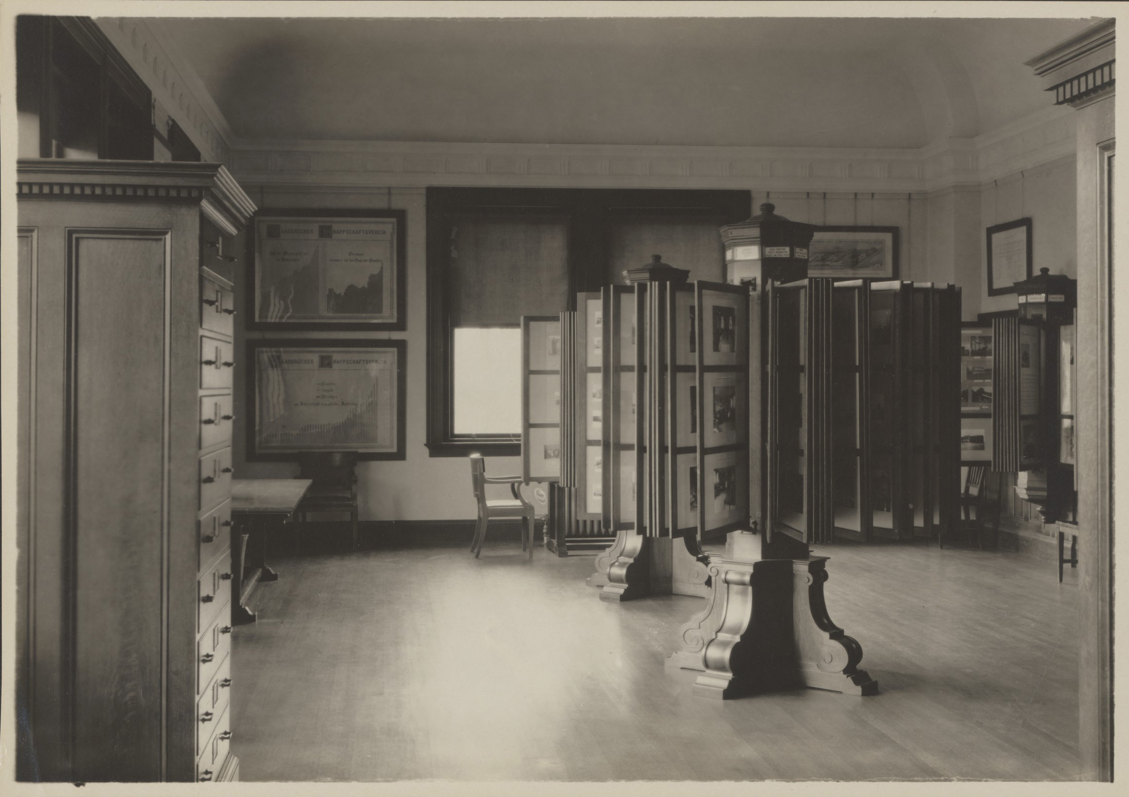 This black and white photograph shows a room with a wooden floor. In the foreground at left is a bureau with several drawers. In the center of the room is a wooden stand with an ornate base. Above the base is a rotating display of photographs. There is another just like it partially visible. Several large framed diagrams and photographs line the walls.