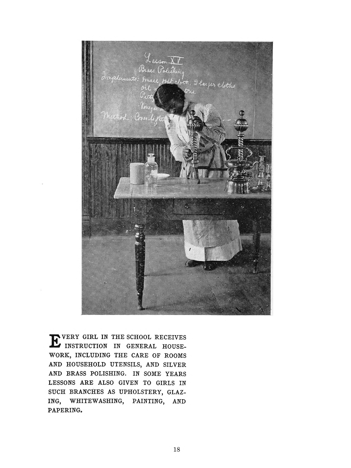 "This page from a book shows a black and white photograph of an African American woman cleaning a silver object on a table. She wears a long white dress with an apron over it. Several other objects on the table as well as a bottle of cleaner. The caption below the image reads ""Every girl in the school receives instruction in general housework, including the care of rooms and household utensils, and silver and brass polishing."""