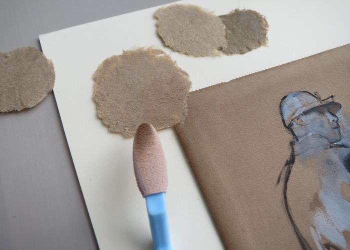 A brown pulp patch is placed over the upper left corner of the drawing, which can be only partially seen. The brown of the patch matches that of the drawing's background. A tool with a blue handle and a soft pink sponge at its end is shown held over the patch. The tip of the sponge is a brown color that matches what is in the patch and the drawing.
