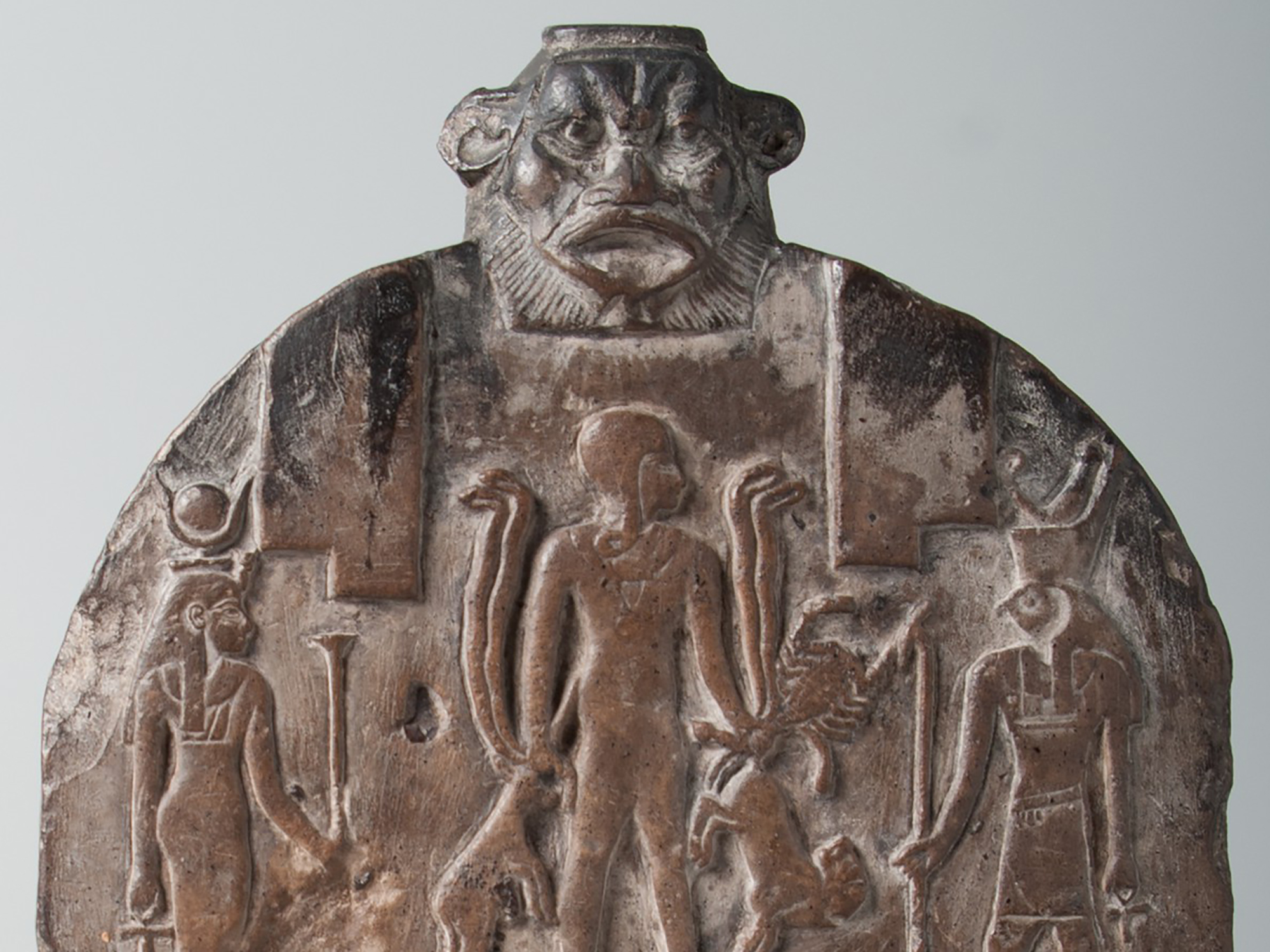 A round-topped limestone slab has two horizontal registers. The upper register depicts the god Horus as a child, holding snakes, a scorpion, a lion, and an oryx; he is standing on two crocodiles. To the left of him is his mother Isis, who wears a long dress and a crown of cow's horns and a sun disk. To the right is Horus as an adult, who has a falcon's head. The lower register shows the goddess Taweret, who has the face and body of a hippopotamus, the paws of a lion, and the tail of a crocodile. She faces a bald man who makes offerings to her.