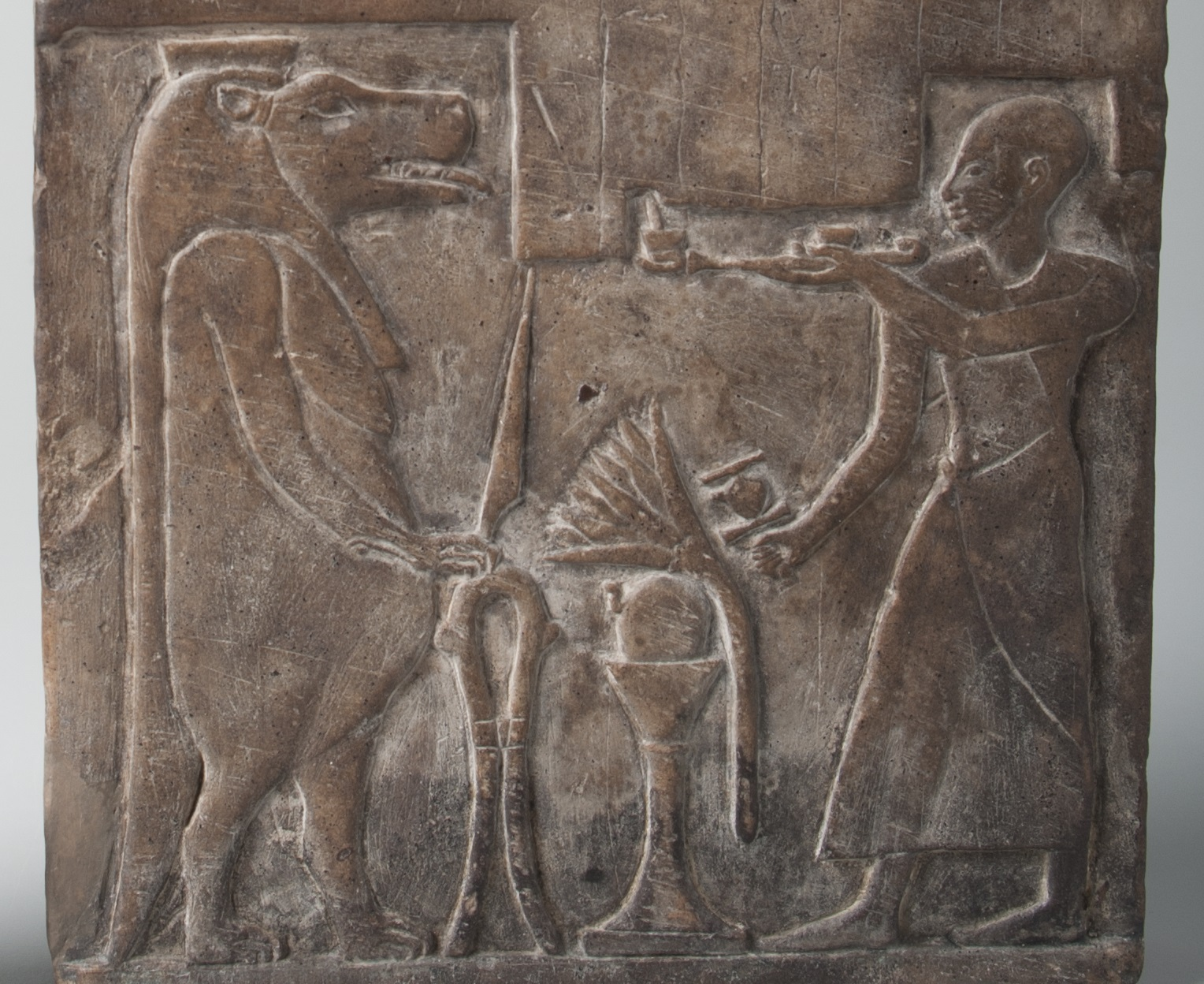 This image shows the lower register of the stele, featuring a bald man in front of the goddess Taweret, who has the face and body of a hippopotamus, the paws of a lion, and the tail of a crocodile.
