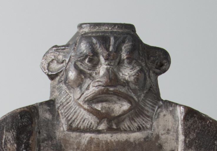 This image of the top of the stele shows the head of the god Bes, with the features of a lion. The head protrudes from the top of the stele in three dimensions, above the upper register.