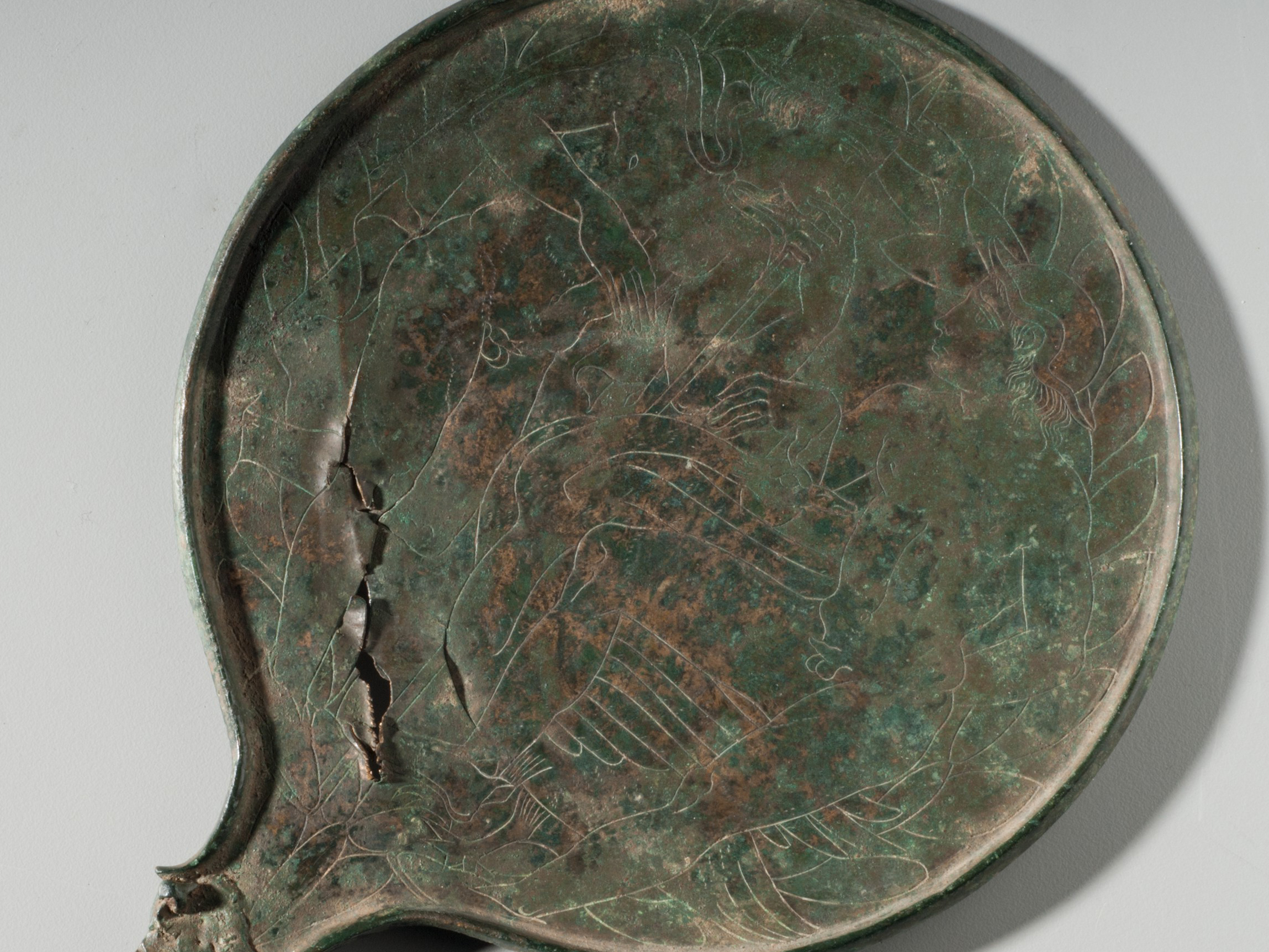 This image shows the reverse of a bronze handheld mirror with a lightly incised decoration. The main body is round with a raised edge, and there is a long, diagonal tear on the lower section. A tang extends from the body but there is no handle.