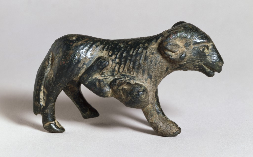 A small brass figurine depicts a woolly ram with a long tail. A bearded man pokes his head out from under its belly, grasping the animal's side with his left arm. The animal's fur is indicated by striated lines. The surface is shiny and nearly black, and partly covered in light brown encrustations.