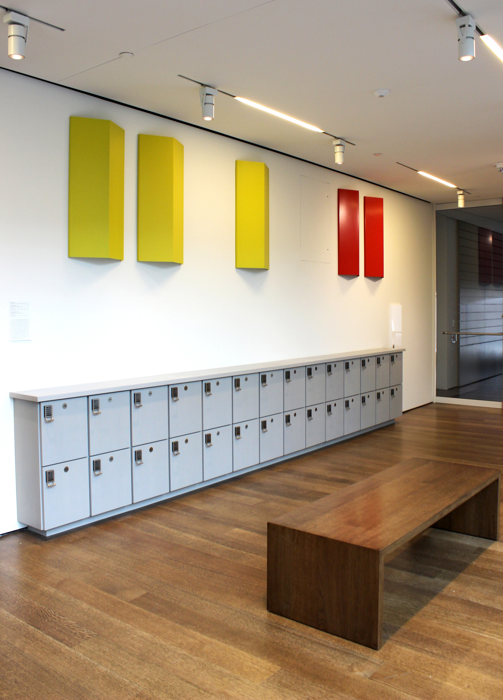 On a white wall, three identical, yellow-painted aluminum sheets are mounted next to two identical, red-painted aluminum sheets, each folded convexly. The folded rectangular sheets, mounted vertically and parallel to each other on the wall, are situated above a row of grey storage lockers. A wooden, rectangular bench stands in the foreground.