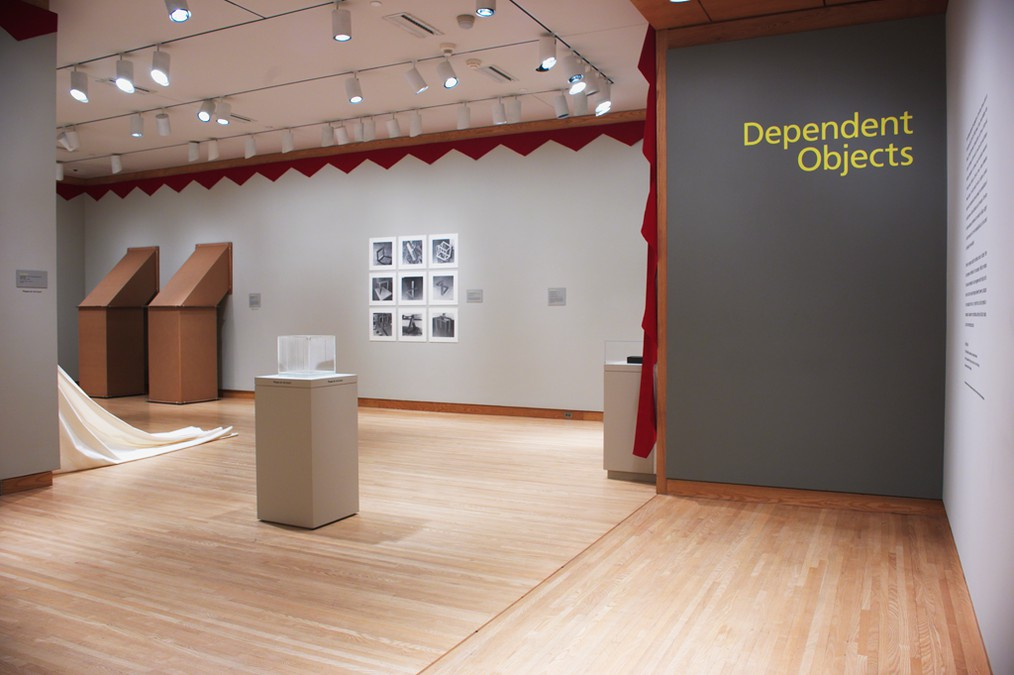 "A museum exhibition installation shows sculptures on pedestals, sculptures extending out from the wall, and photographs. On the far right, the title of the exhibition, ""Dependent Objects,"" appears in large yellow font against a gray wall."