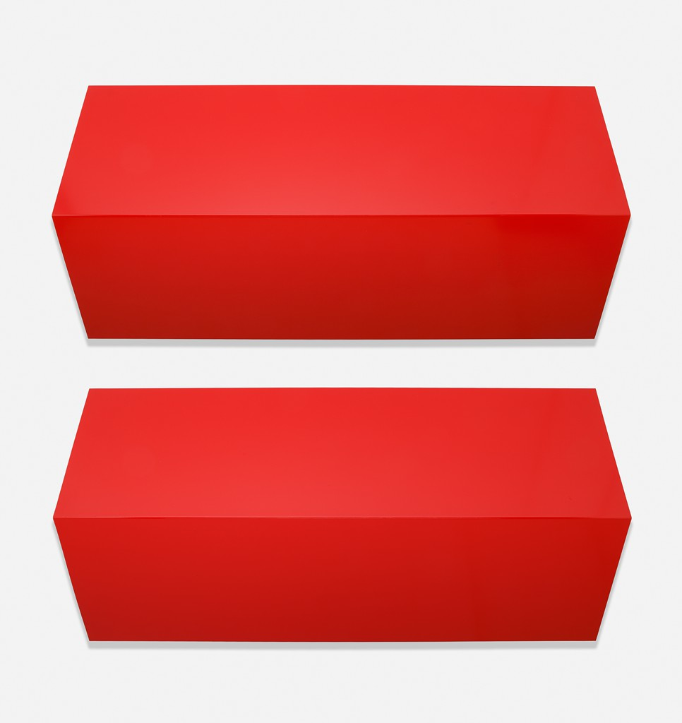 Two identical, red-painted aluminum sheets, each folded convexly, are mounted and oriented horizontally on a wall.