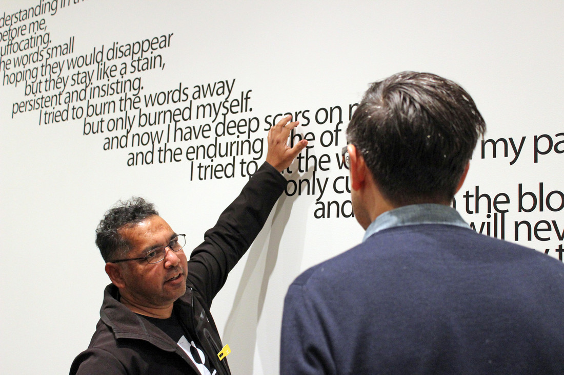 "Two indigenous men stand in conversation. Facing the camera, the artist gestures to the word ""scars,"" as part of an installation of black words along a white wall."