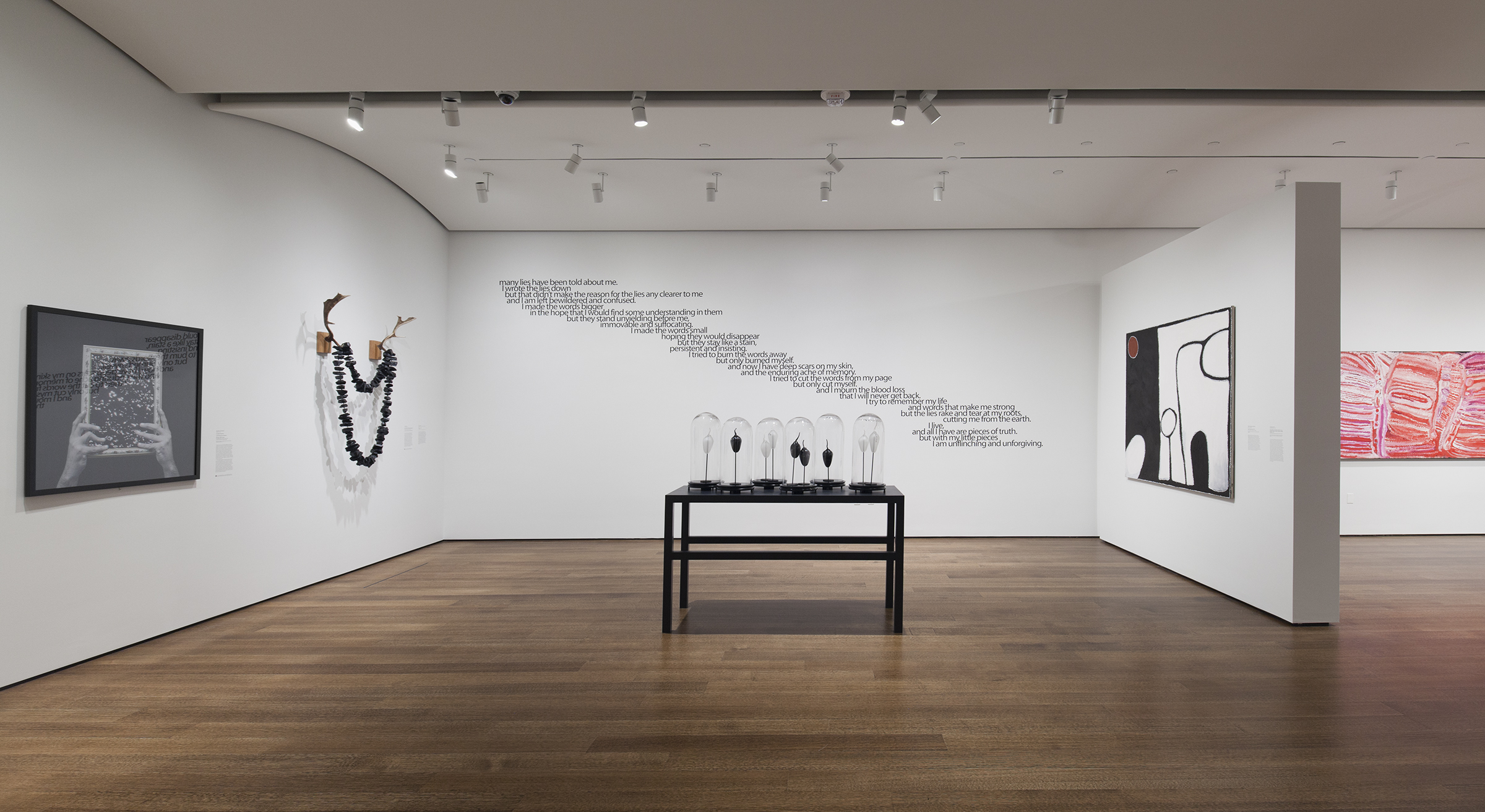 """Exhibition gallery featuring a variety of artworks. In center of gallery is a sculpture consisting of a black table covered with glass """"specimen"""" cases. Black text is installed across the back wall (like a scar). On the left wall is a black-and-white photograph of two hands holding a square object and a sculpture consisting of a set of antlers with a giant necklace composed of coal. On the right, is a black, white and red abstract painting."""