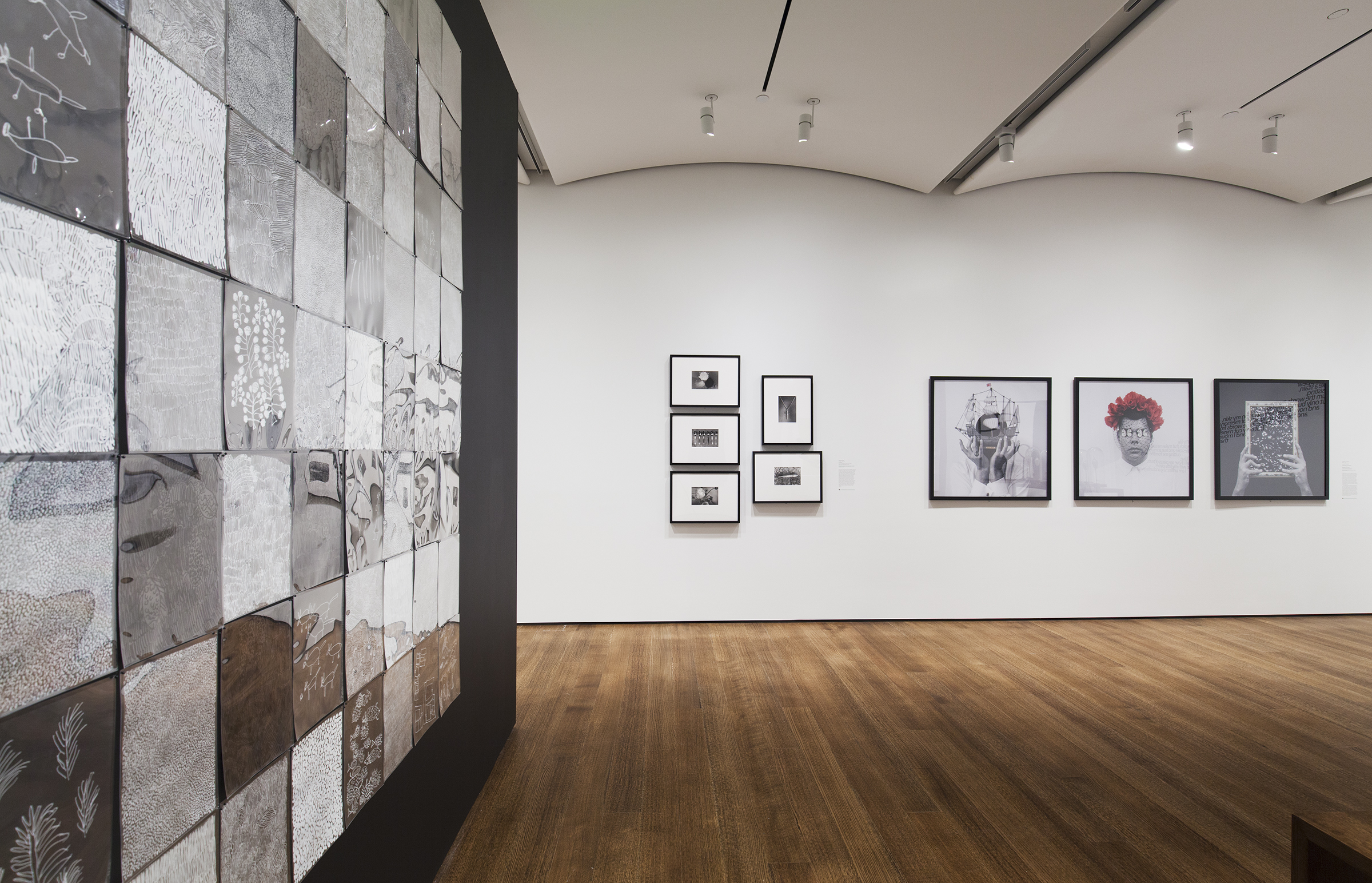 Exhibition gallery with a grouping of photographs on the back wall. On the left, is a black wall with a series of square black and white prints installed.