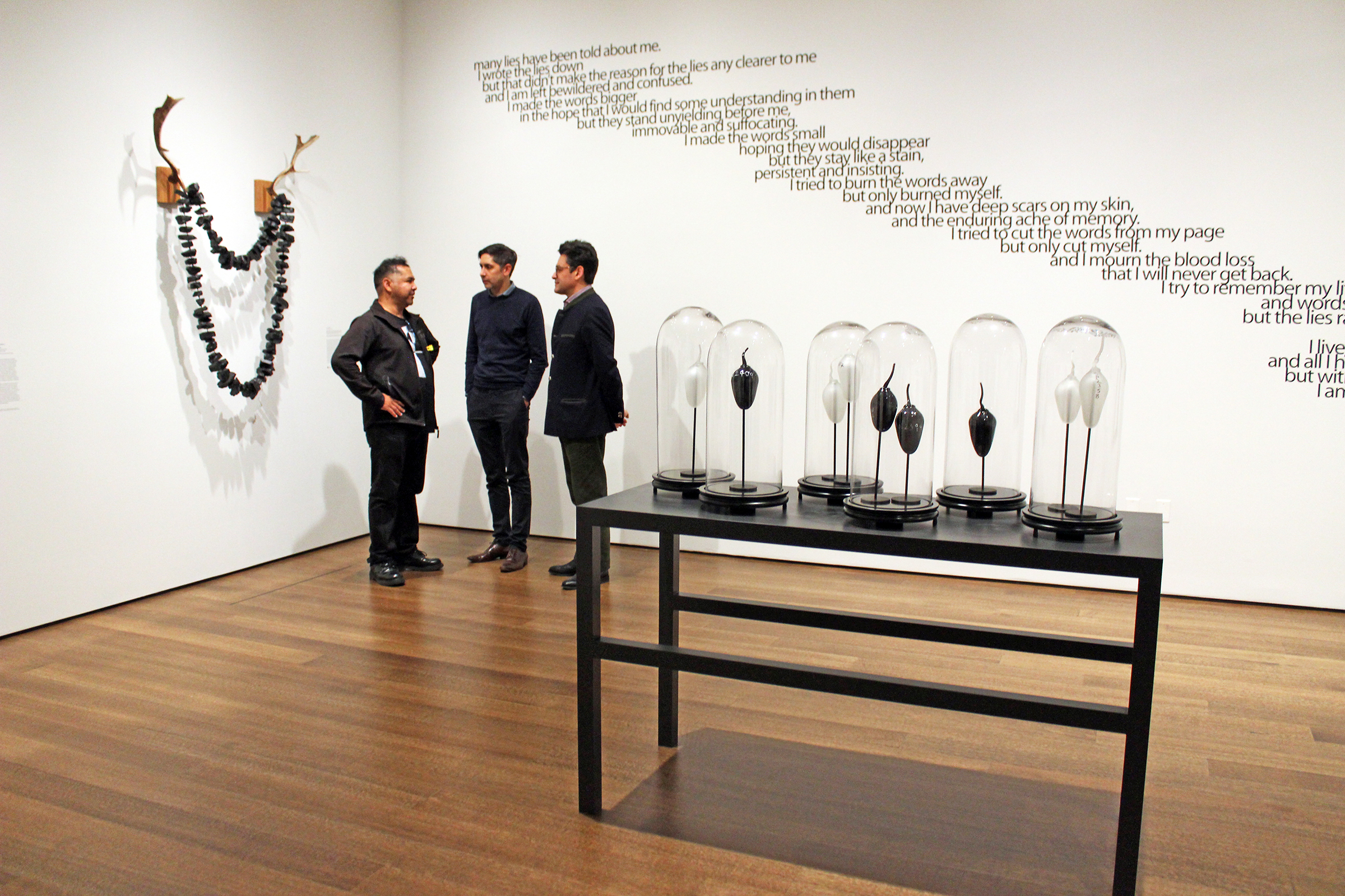 """Three men stand in the corner of an art gallery in conversation in front of a white wall with black text. In the middle of the gallery is a sculpture of a black table covered with glass """"specimen"""" cases. To their left, a large sculpture hangs from the wall, consisting of a set of antlers with a giant necklace composed of coal."""