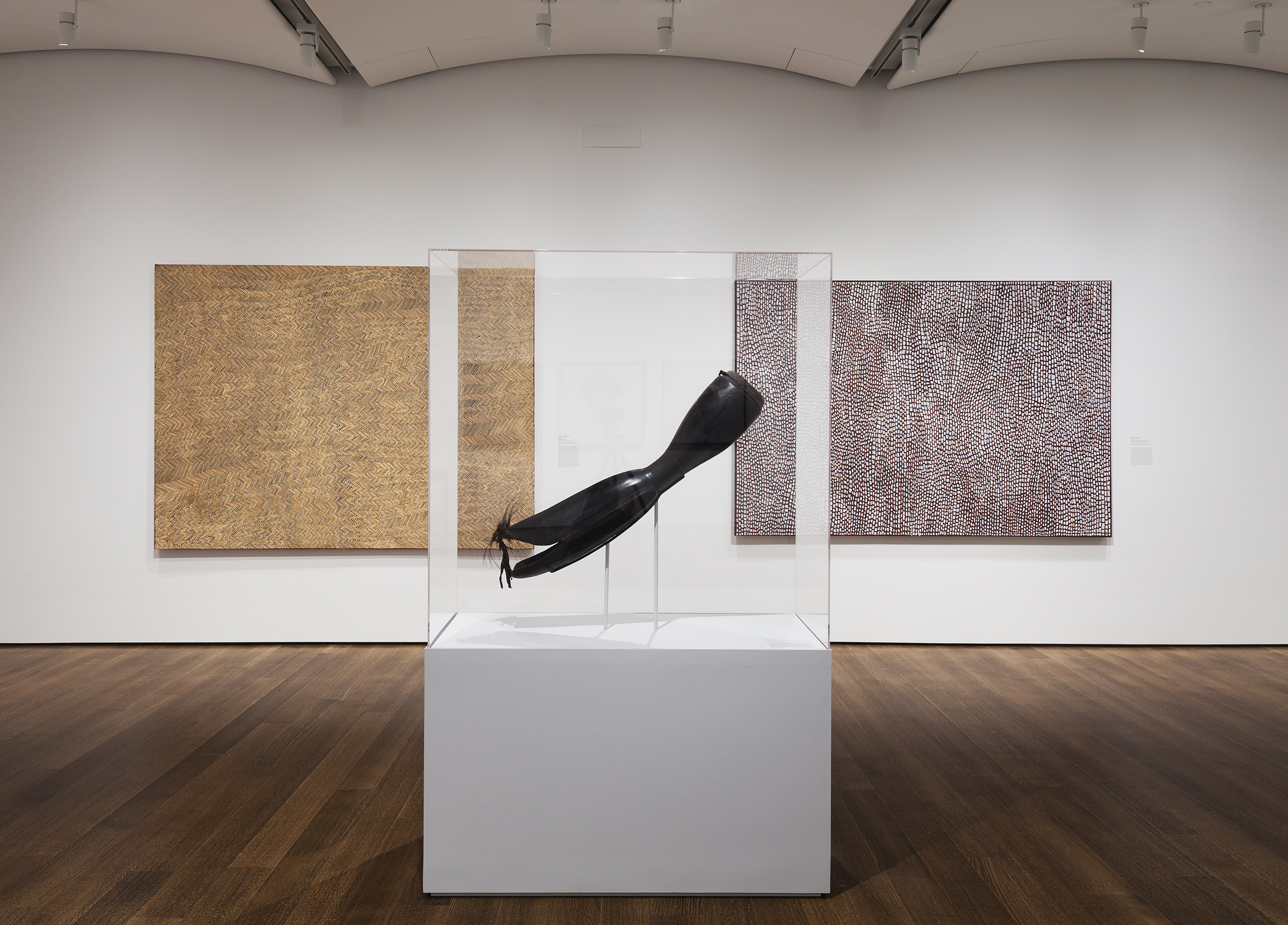 Exhibition gallery featuring large Warup drum in a glass case centered in the foreground. Behind the drum on the wall are two large scale white and brown abstract paintings by Australian indigenous artists.