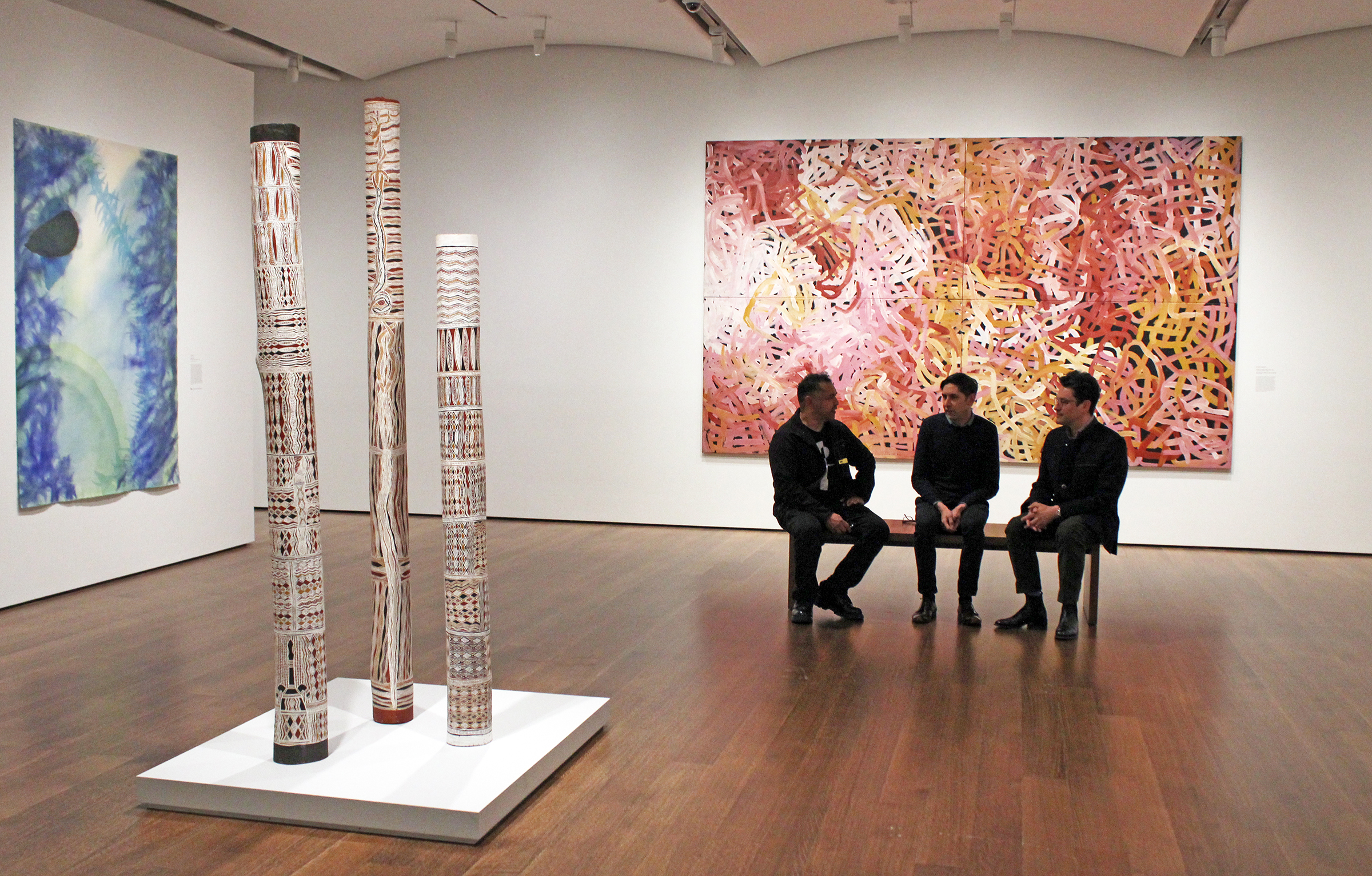 Three men sit on a bench in the middle of the exhibition gallery, in front of a colorful abstract painting of red, white, yellow and pink swirls.