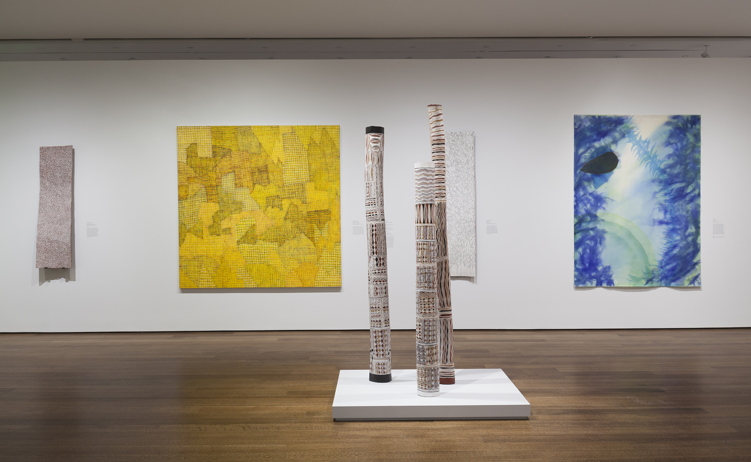 Gallery with three tall carved bark sculptures in the center.  Hanging on the wall in the background are four colorful abstract paintings by Australian indigenous artists.