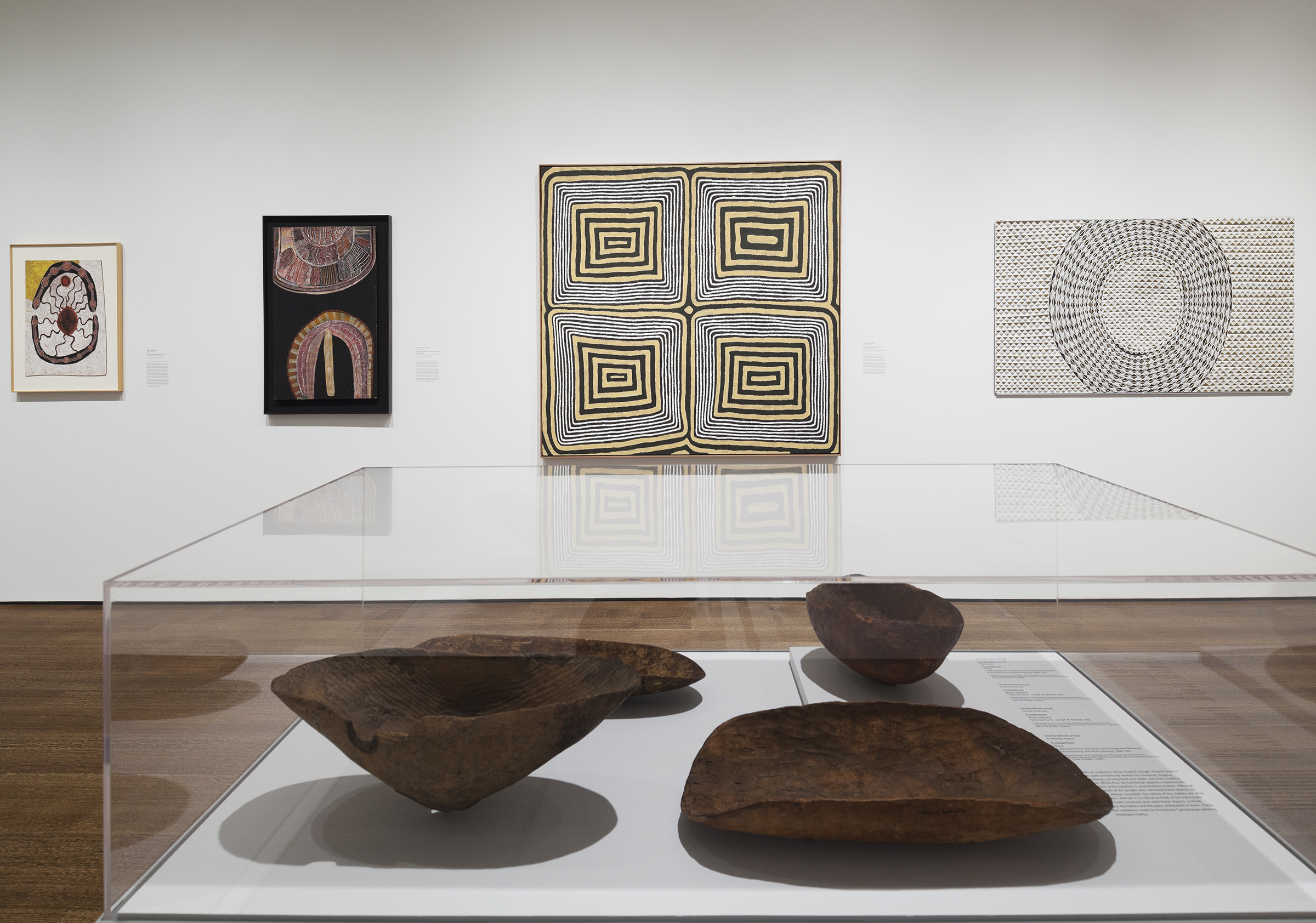 In the foreground of a gallery, a glass case with four wooden bowl like objects are on display. Hanging on the wall in the background are four bright abstract paintings by Australian indigenous artists.