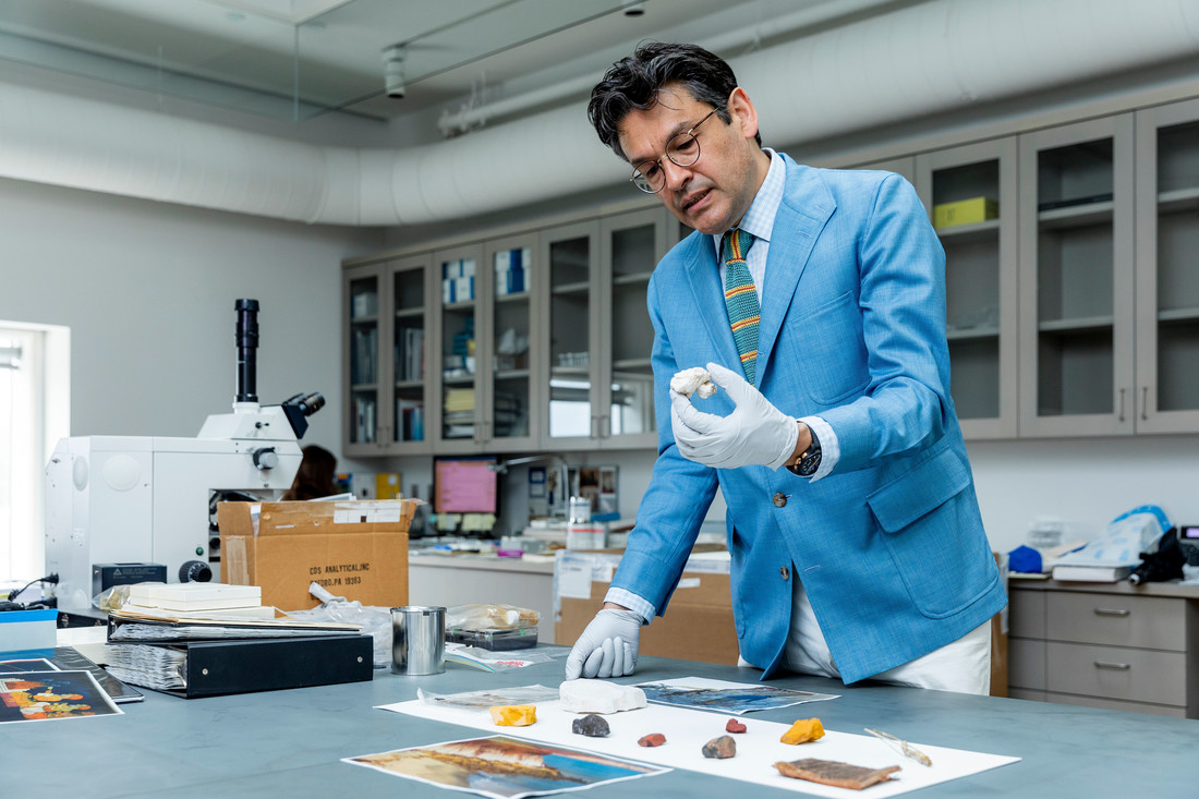 Man in a blue suit is standing in a laboratory with a sample of large colorful pigments on a cloth before him. He is holding a large white chalky pigment in his hand.