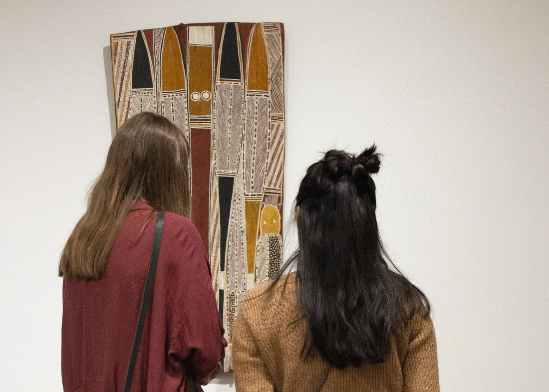 Two young women view colorful bark painting consisting of linear shapes and lines in earth tones.