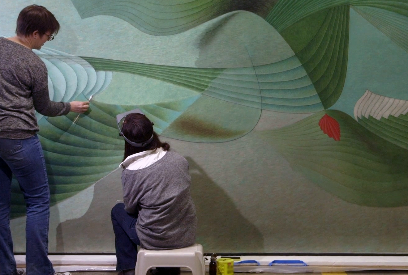 Two people, whose backs are to us, are in front of a large-scale abstract painting. The person on the left is standing and is applying a long cotton swab to the painting. The person on the right is wearing a visor and sitting on a stool. The painting consists of interlocking ribbed curves in shades of green against a lighter green background, punctuated with smaller red shapes.