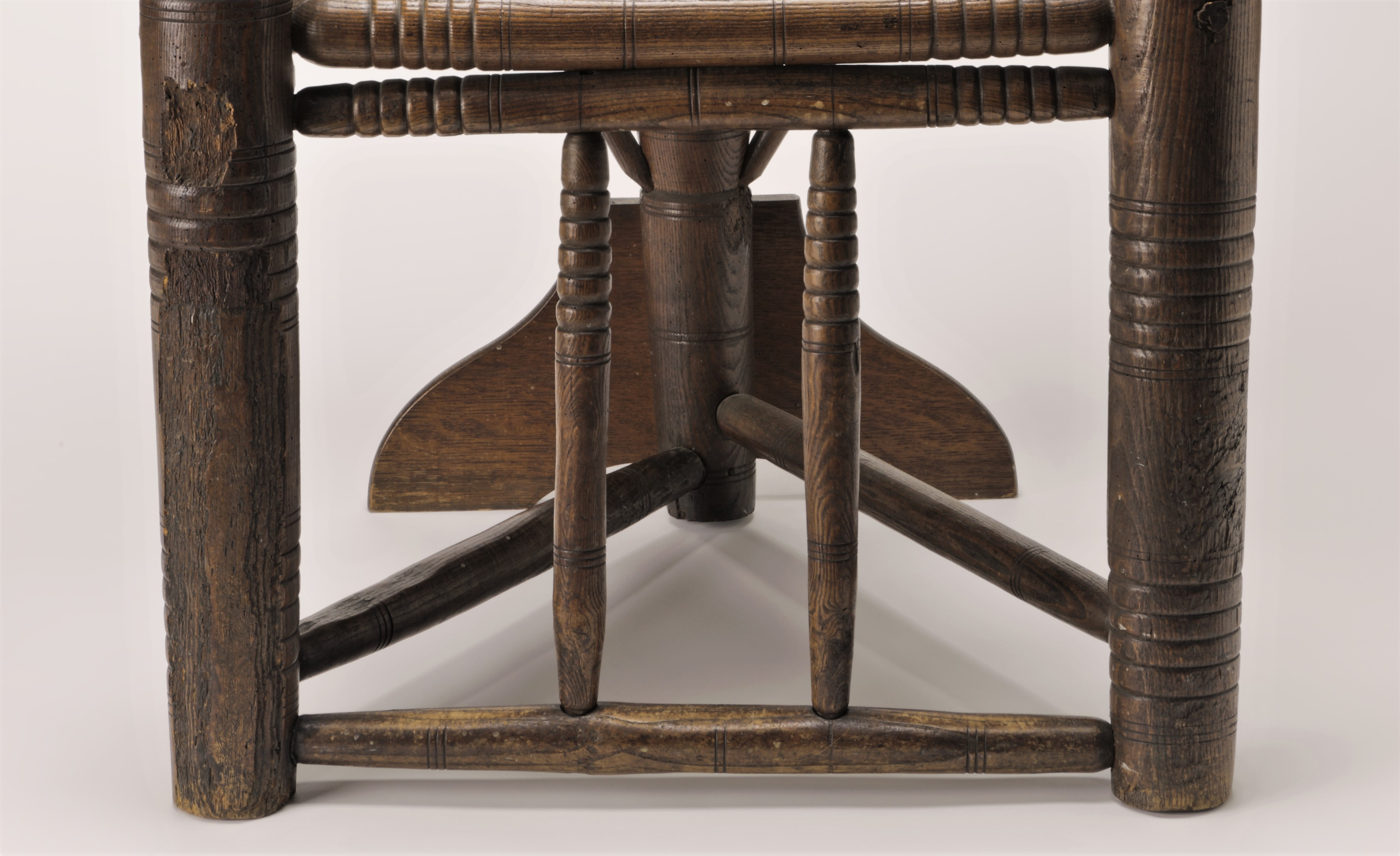 This image shows the bottom half of a wooden three-legged chair. Two thick legs stabilize the chair in front with horizontal lines carved into each at various heights. The leg on the left side of the image shows damage or loss to the surface. A third leg is at the back of the chair. Just above the ground are three spindles, each connecting the legs, forming a triangular shape. Two horizontal spindles decorate the chair inside and are parallel to the two front legs.