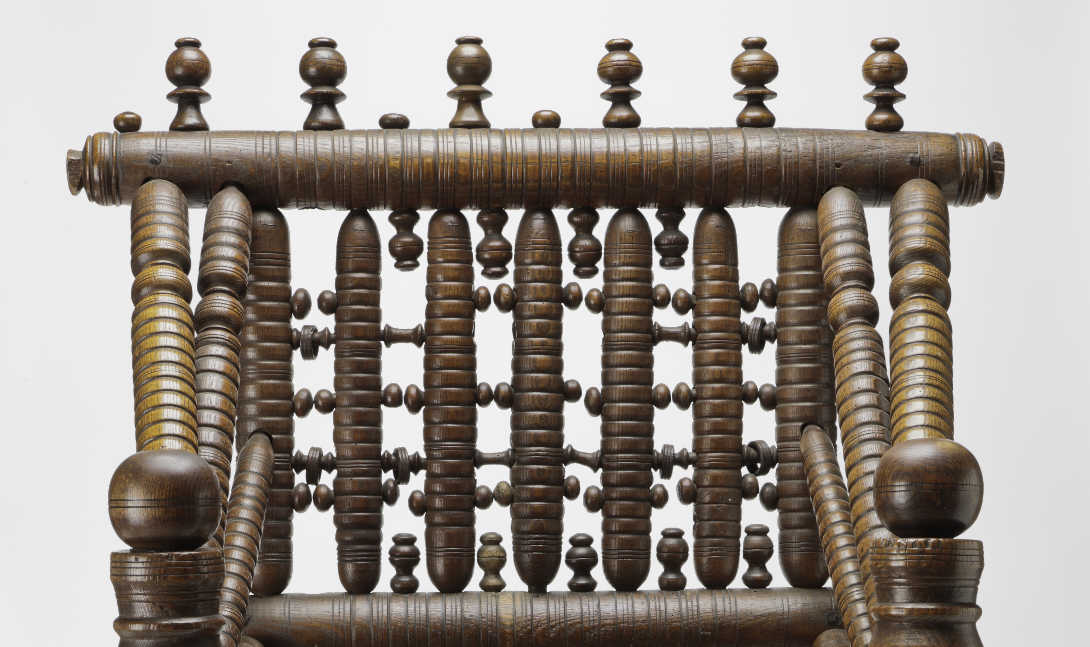 This image shows the back of a wooden three-legged chair. The most prominent elements of the chair back are six vertical spindles topped by a thick horizontal spindle. Atop this are six carved, vertical decorative pieces. Smaller pieces of similar shape are interspersed vertically and horizontally along the back. There are several gaps along the back.