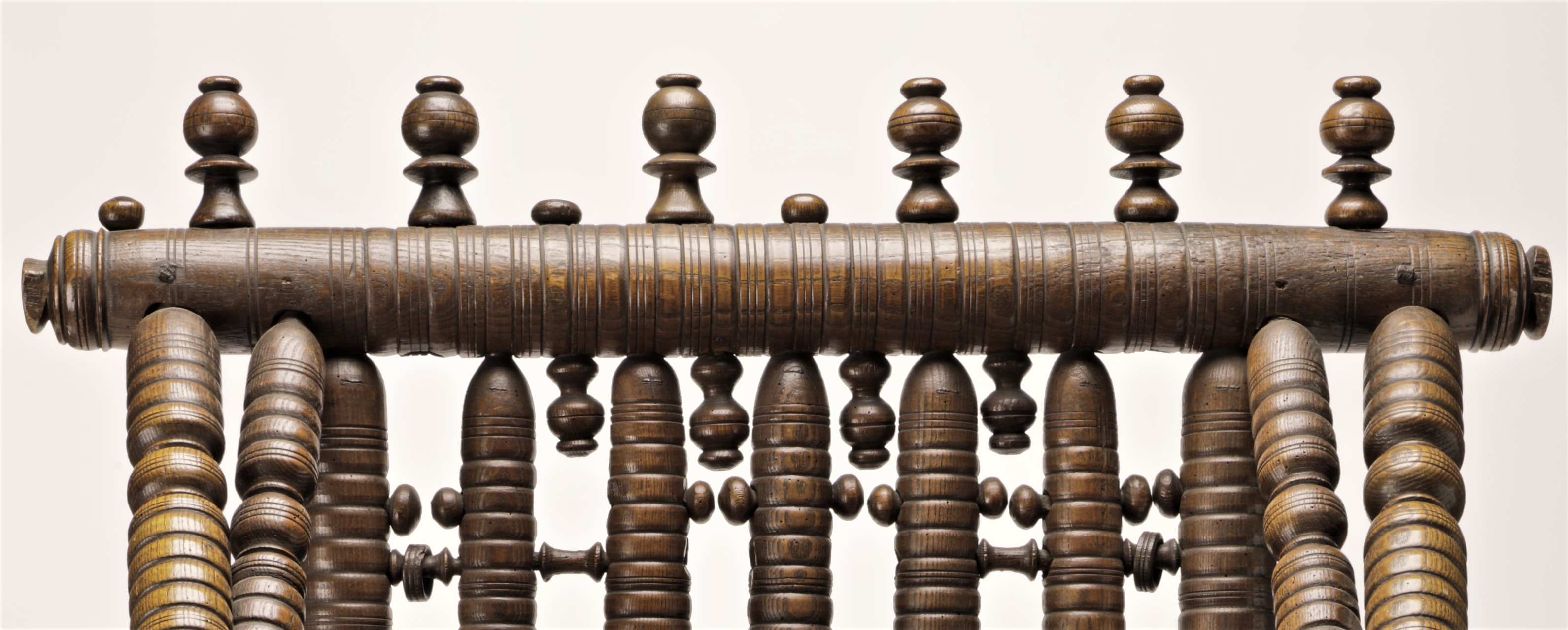 This image of the chair shows a thick horizontal spindle with decorative details at the top, with several pommels of various lengths and widths above and below it. Six vertical spindles are below the large spindle. Between them, small circular and oval shaped knobs are interspersed, as are a few small rods that connect between spindles. Two of those rods have circular wooden rings attached.