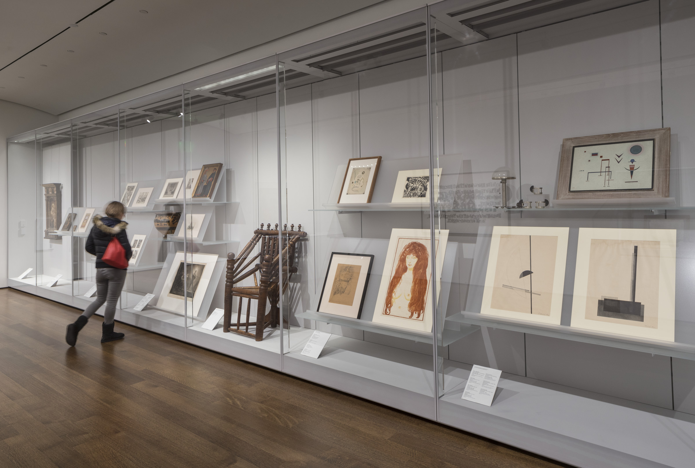 In this photograph of a gallery, several artworks and objects of various sizes appear in a floor to ceiling gallery case enclosed by glass. Near the center of the case is the wooden three-legged chair. A person wearing a hooded jacket and jeans approaches the glass case.