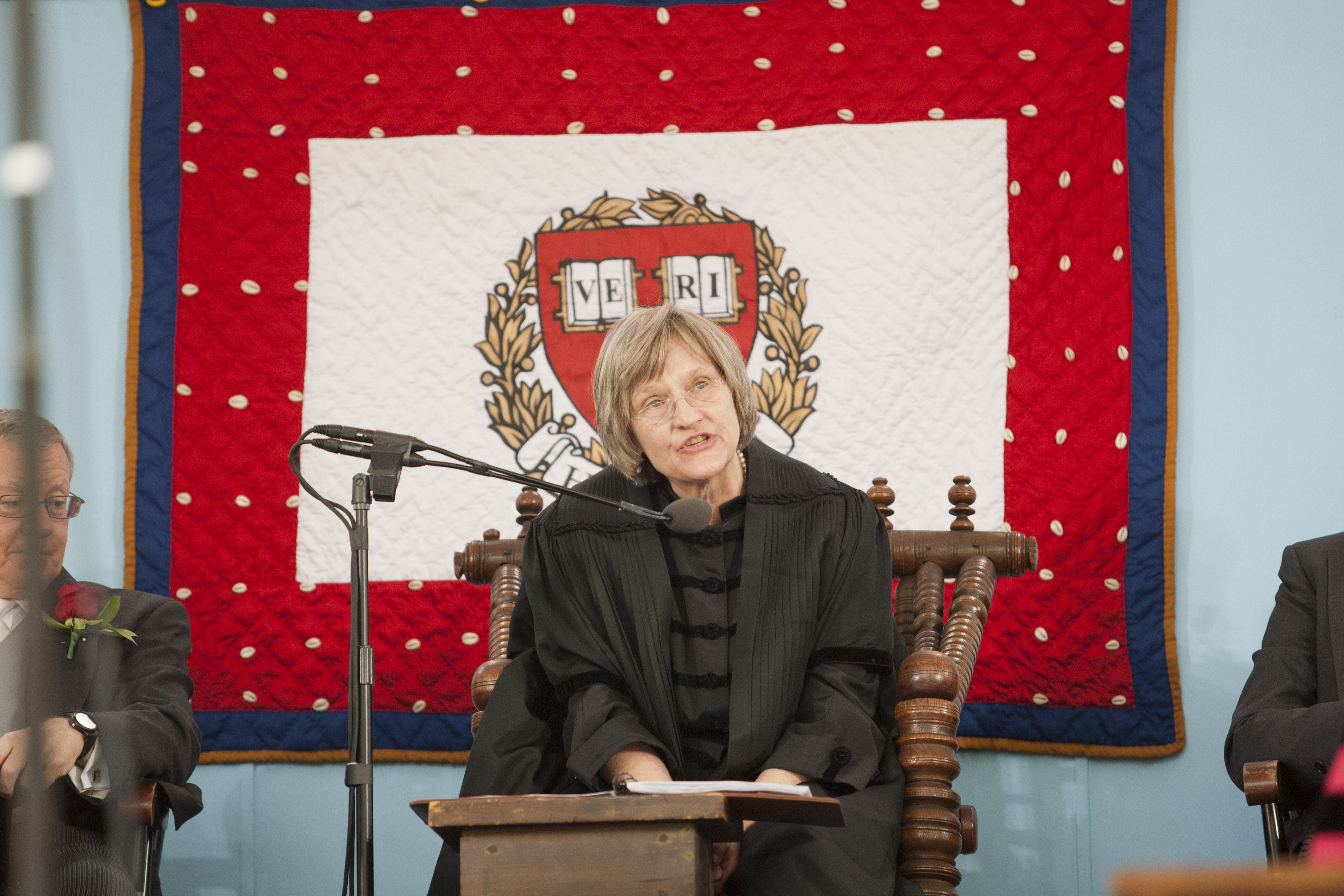 """Drew Gilpin Faust sits in a wooden chair (the President's Chair) wearing black robes and speaking into a microphone. In front of her is a small wooden table that appears to have pieces of paper on top of it. In the background hangs a quilt with a thin navy border on the outside and a wider red border with white dots on the inside. In the center of the quilt is a white rectangular block with an illustration of a red crest, surrounded by branches of yellow leaves. Two blocks of white in the shape of books are inside the crest; the first reads """"VE"""" and the second reads """"RI."""""""