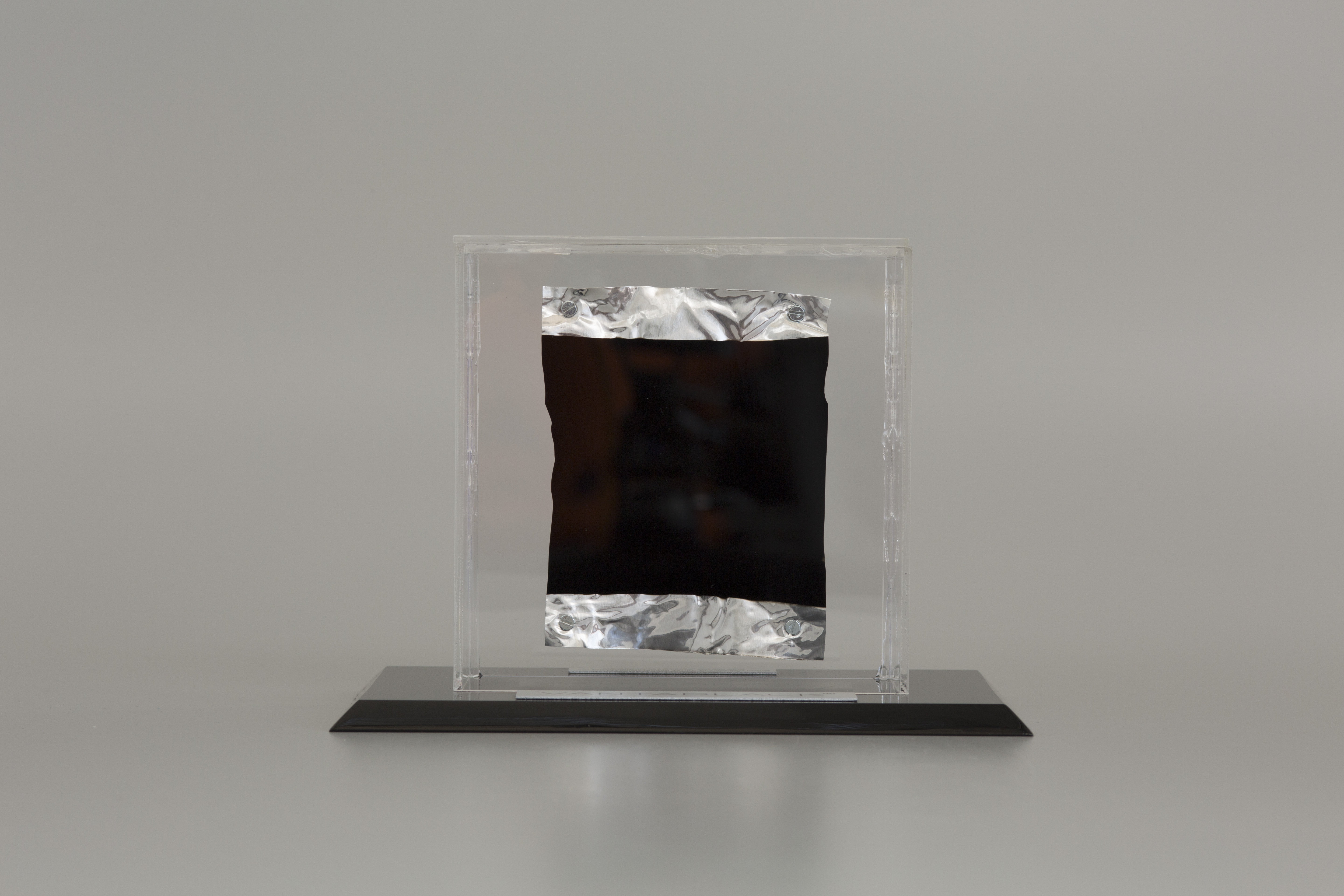 This photograph shows a piece of aluminum foil with a black square on it. The foil is inside a block of glass with a pedestal.
