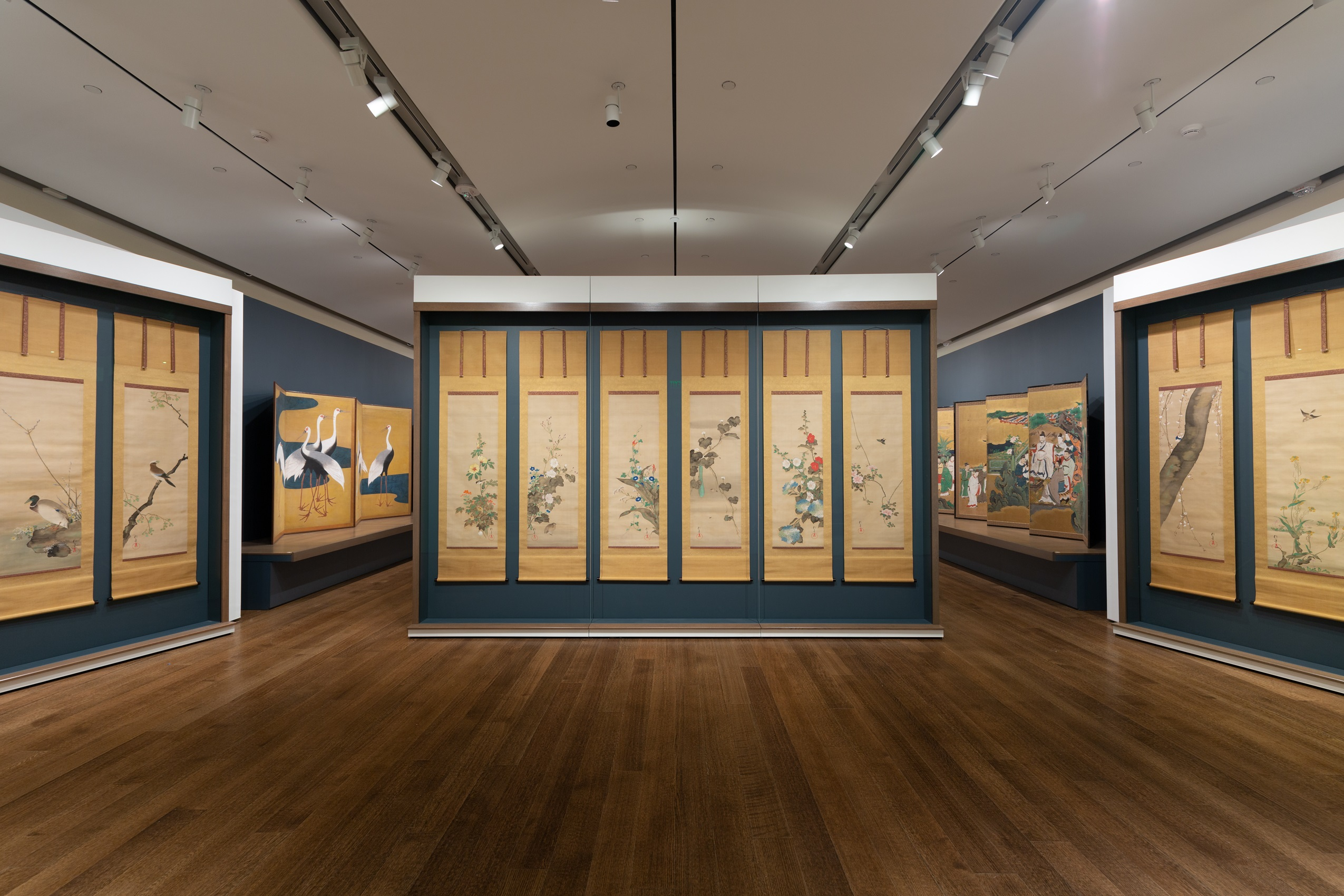 In the center of a gallery is a free-standing wall with a dark bluish-gray trim, upon which are six vertically oriented hanging scroll paintings. The paintings depict colorful birds and flowers and have a cream-colored background. Several other paintings depicting birds and people are mounted on walls situated to the left and right of the center wall.