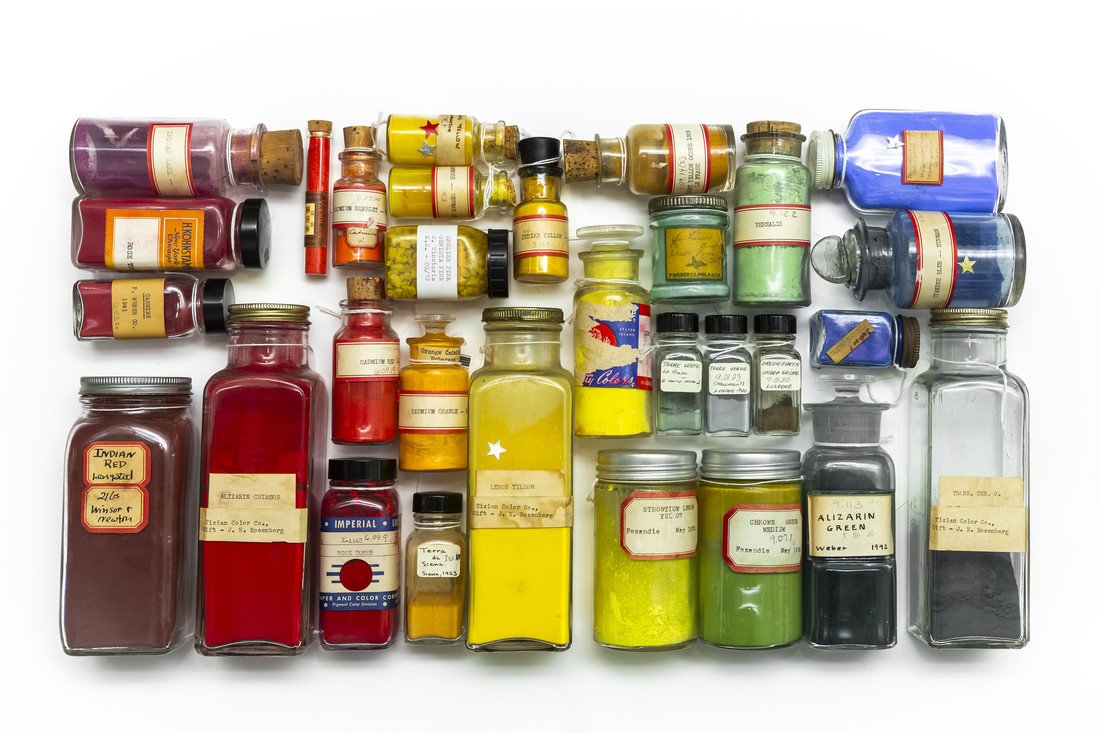 Multiple glass containers, of vastly varying sizes, with a mixture of cork tops and screw-tops are tightly clustered together lying flat on a surface. Each container contains different color pigments.
