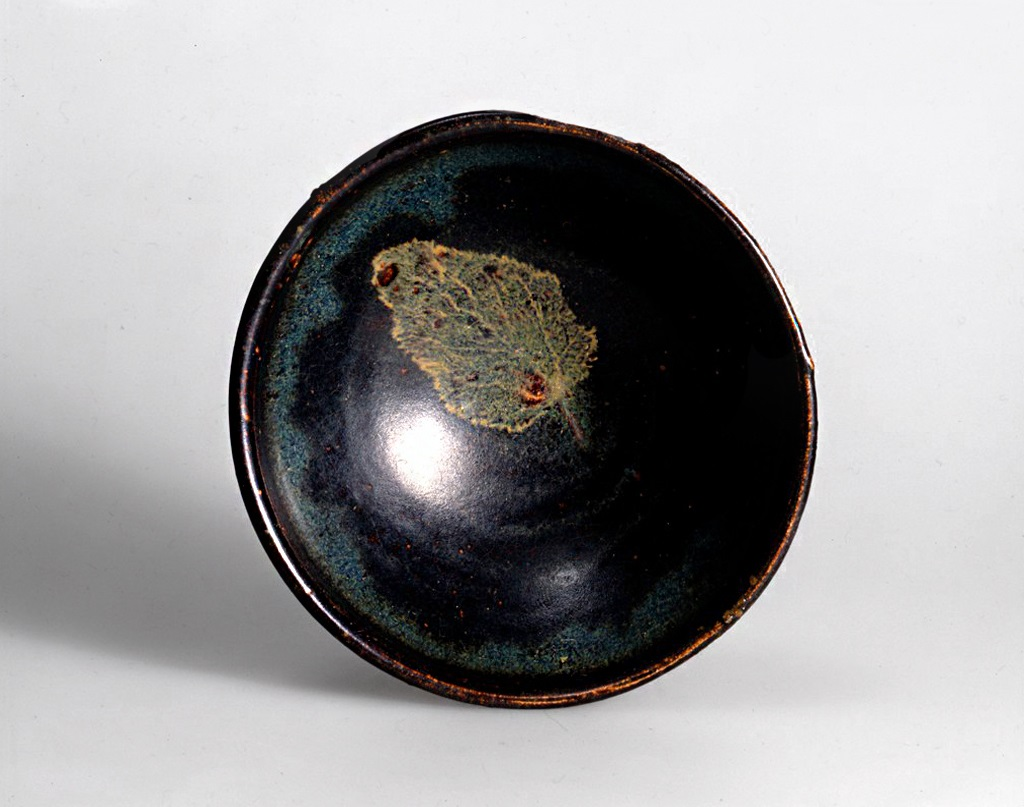 Pictured from above, this small dark brown bowl features the greenish imprint of a leaf in its interior, a bit off-center.