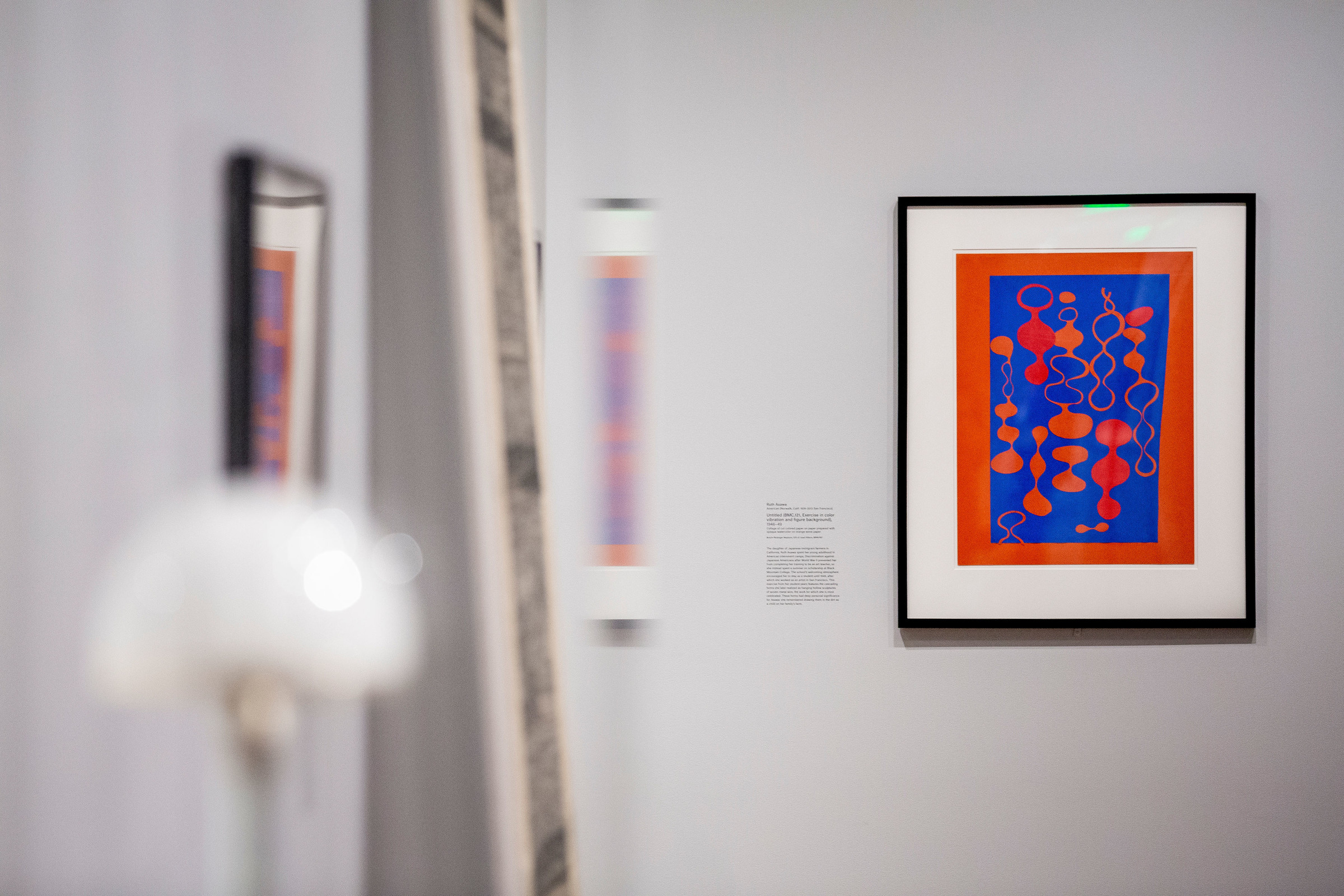 This photograph shows on a gray gallery wall a black-framed collage in the right half of the image. The collage depicts several orange and red biomorphic shapes, some of which are filled in and some outlined, against a blue background. The collage is bordered by red paper, and the mat is white. The remainder of gallery at left appears out of focus.
