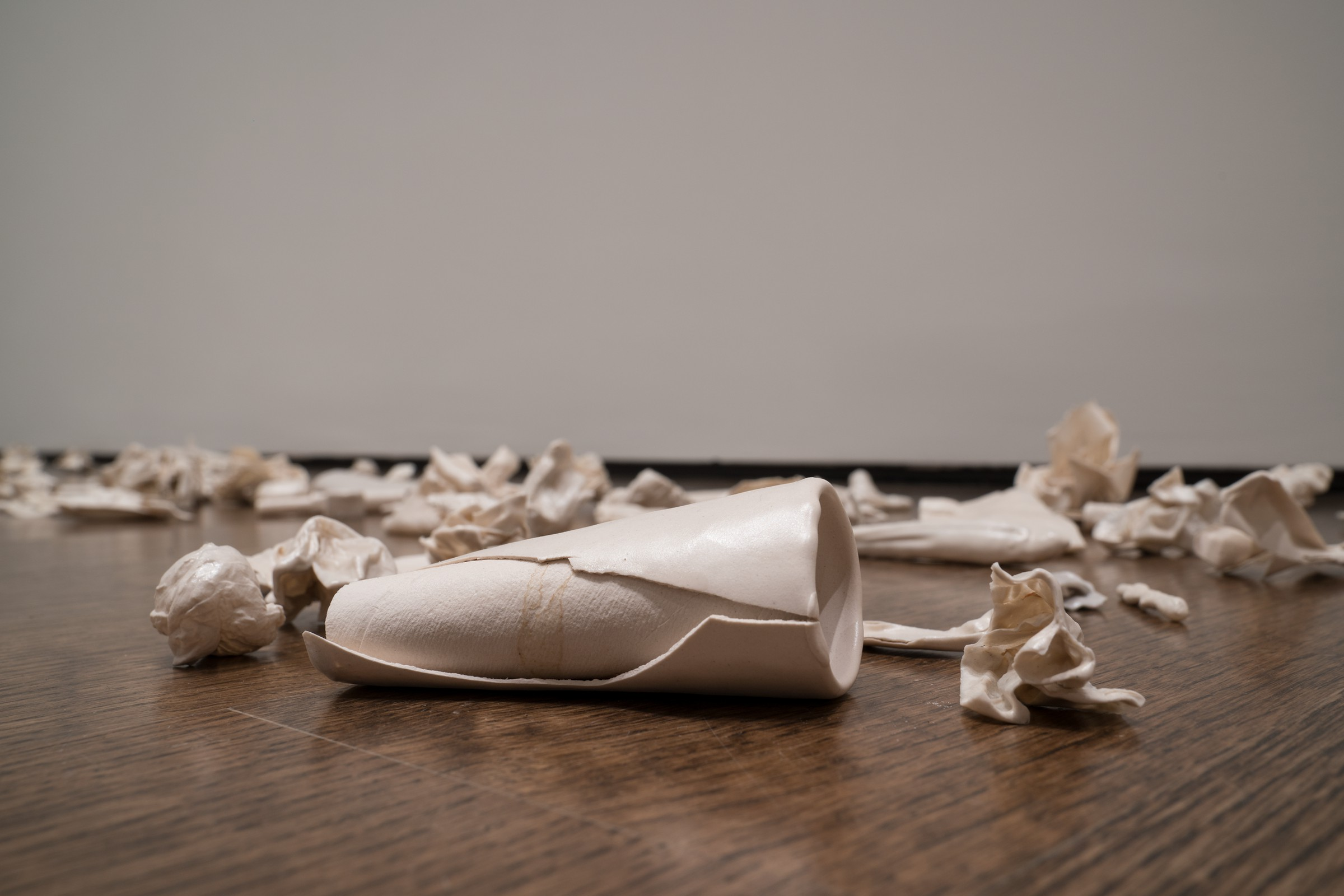 Several white porcelain objects are scattered on a wood floor. Some of the objects are recognizable, such as a toilet paper roll and crumpled and folded pieces of paper.