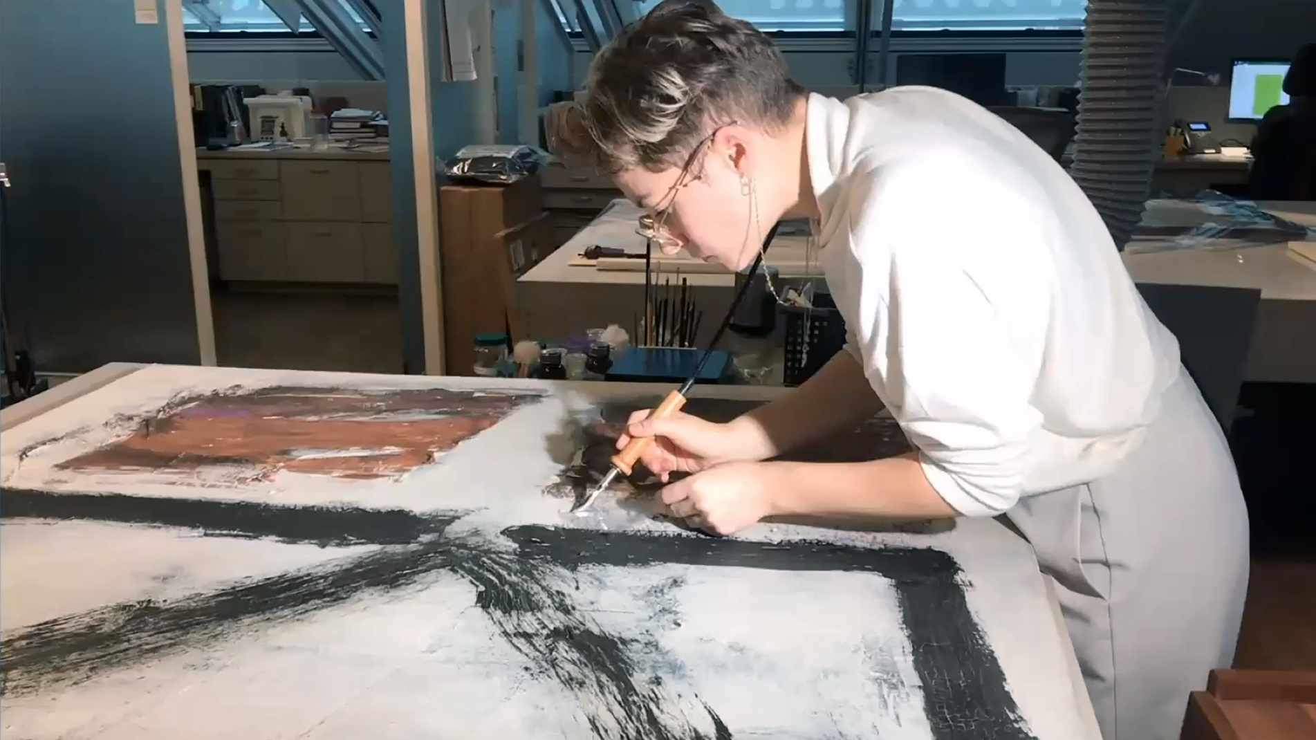 A woman wearing a white shirt and gray pants stands over a large-scale abstract painting in a lab. She applies a white material to the painting using a long slender tool.