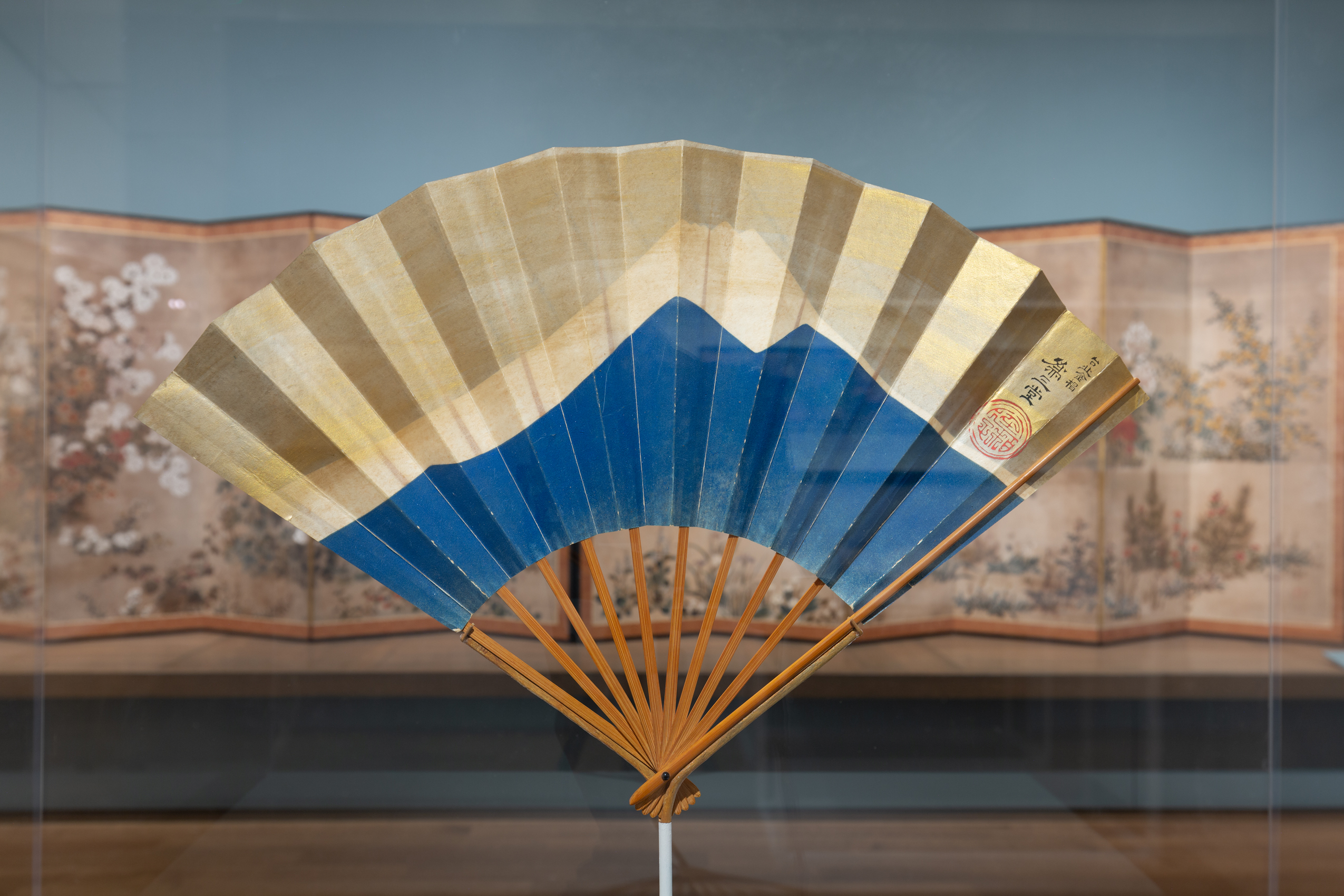 A paper fan is held upright by thin wooden supports on a display in a gallery. The fan features a geometric depiction of a blue mountain with a white-topped peak. The space above the peak is gold. A black and red inscription is on the right side of the fan. A floral folding screen can be seen in the background.