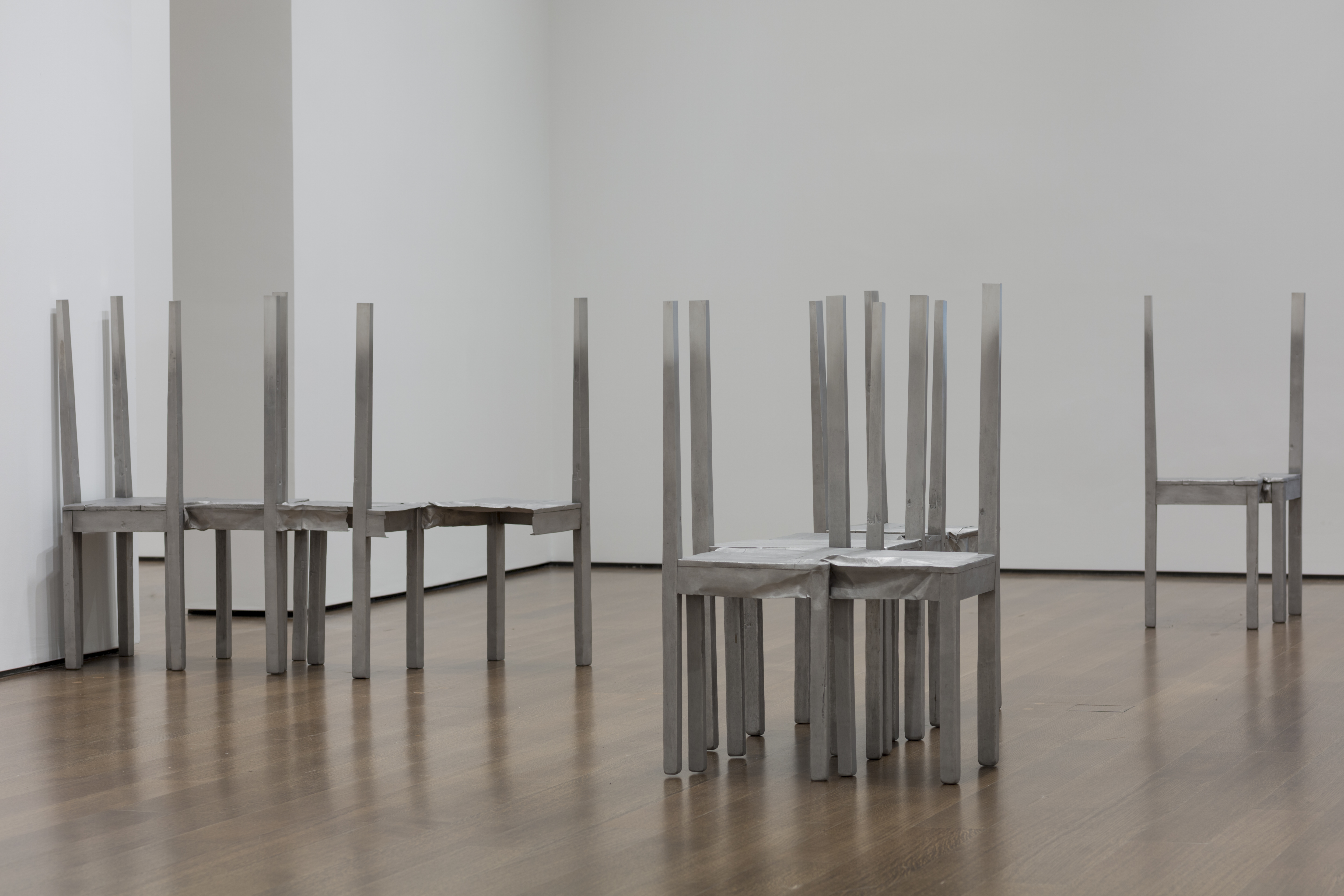 This photograph shows three groups of stainless-steel chairs, crumpled, ripped, and/or merged together. These sculptures are installed in a gallery with white walls and a wood floor.