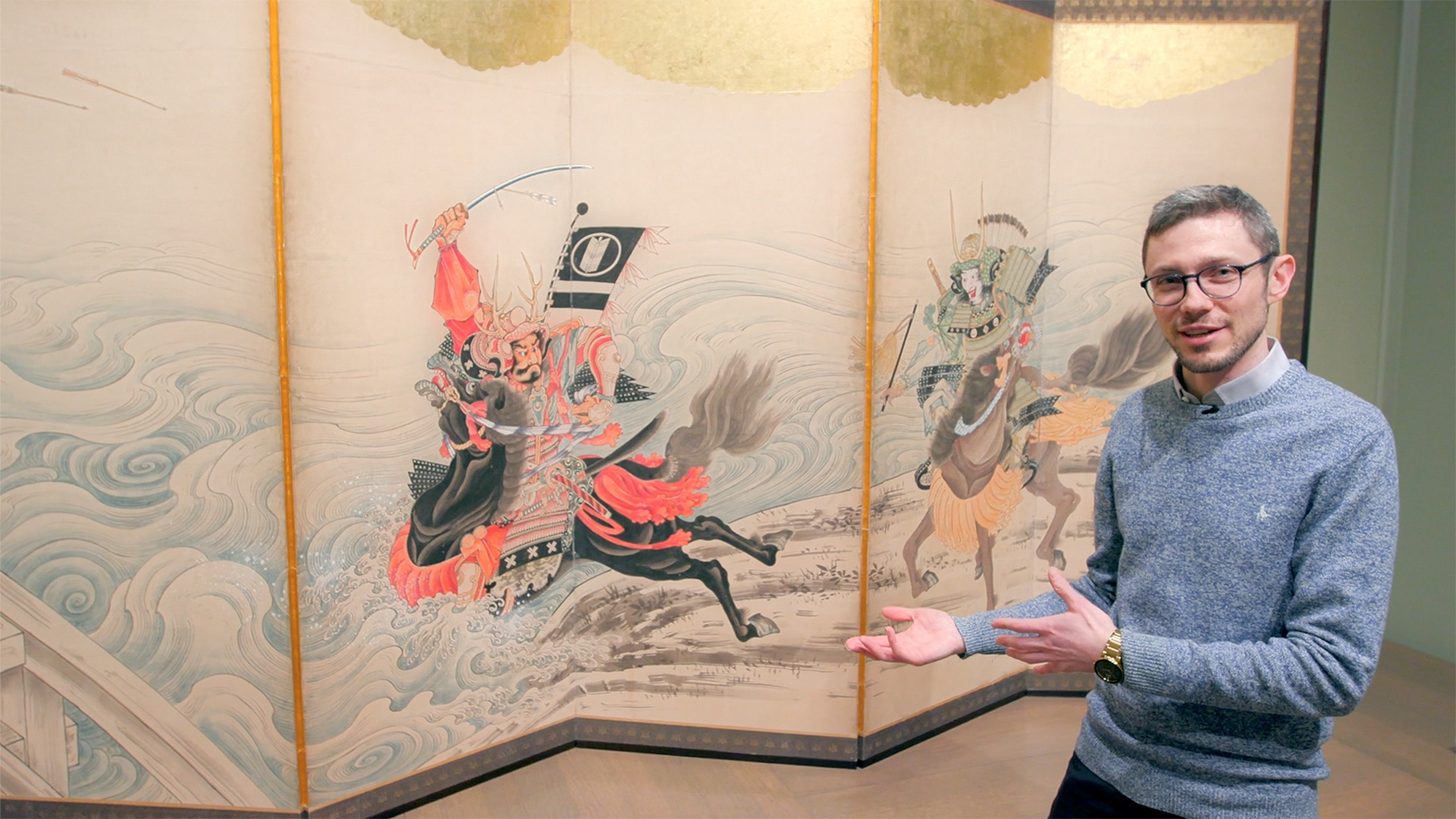 A person with glasses and short hair stands in front of and gestures toward a folded screen. The screen painting shows two warriors on horseback with swords drawn, charging forward.