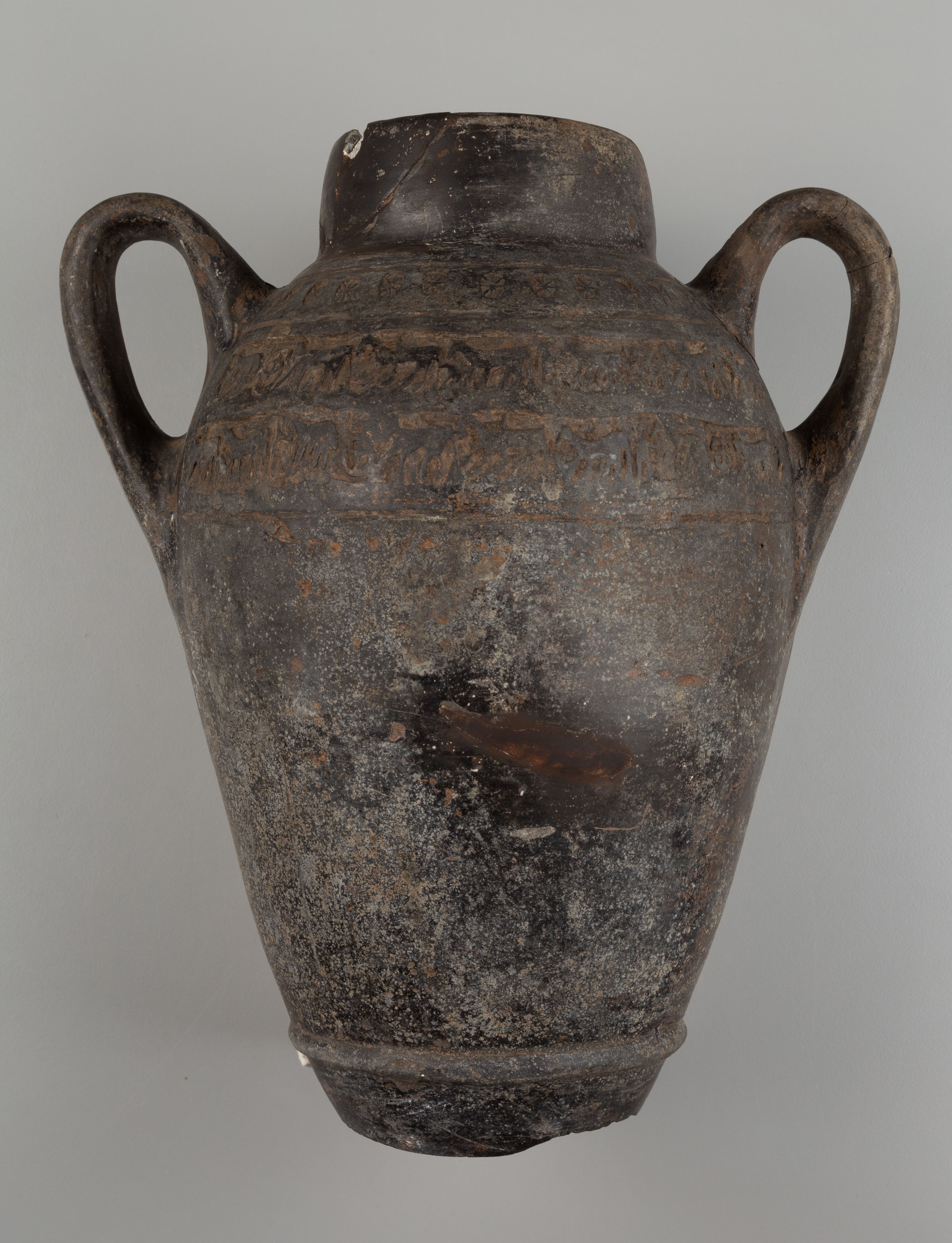 This photograph shows a side view of a vessel with two curved handles and no base. There are pale surface encrustations and one small area that is darker in color in the center.
