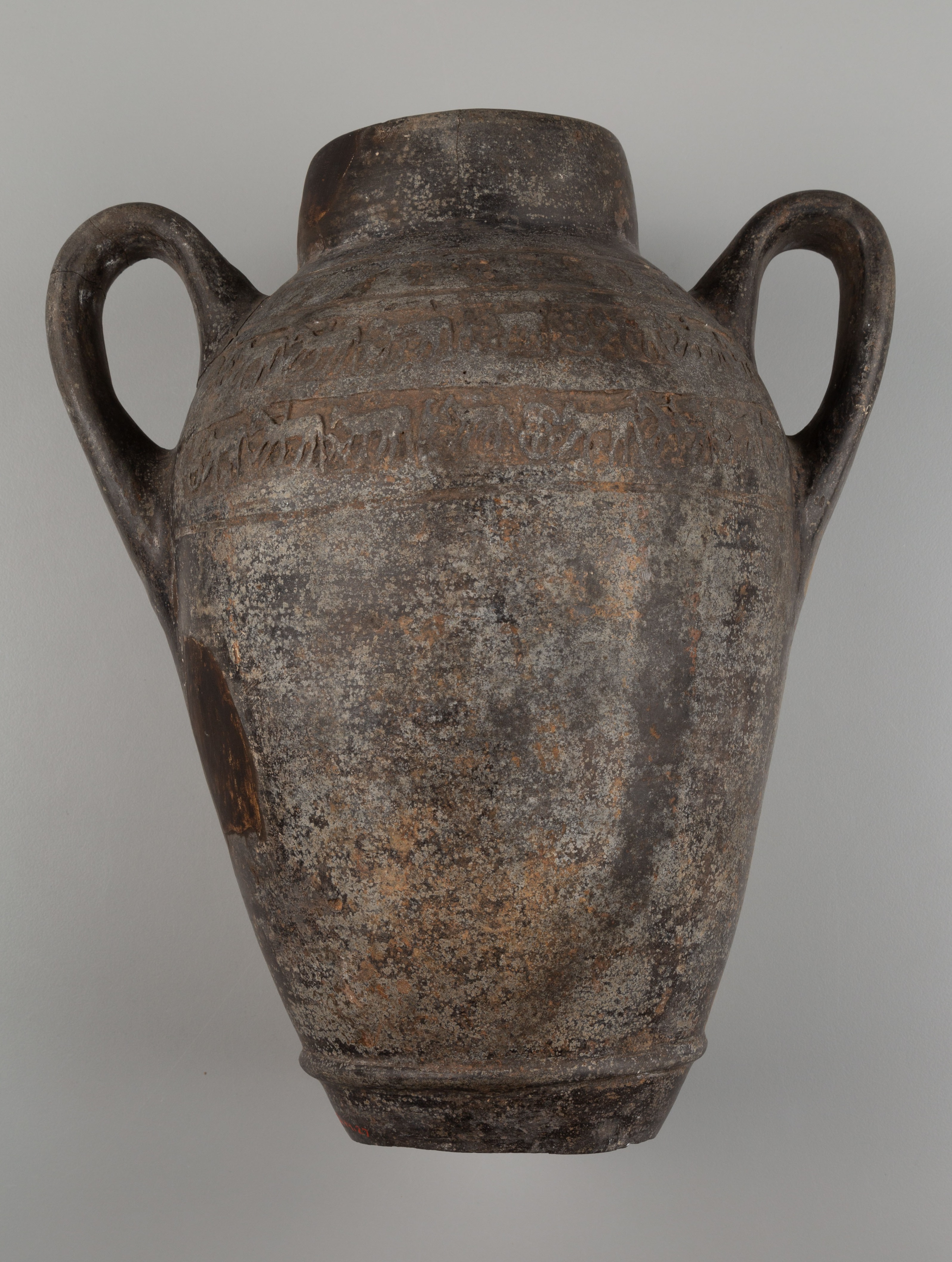 This photograph shows a side view of a vessel with two curved handles and no base. There are pale surface encrustations and one small area that is darker in color on the left.