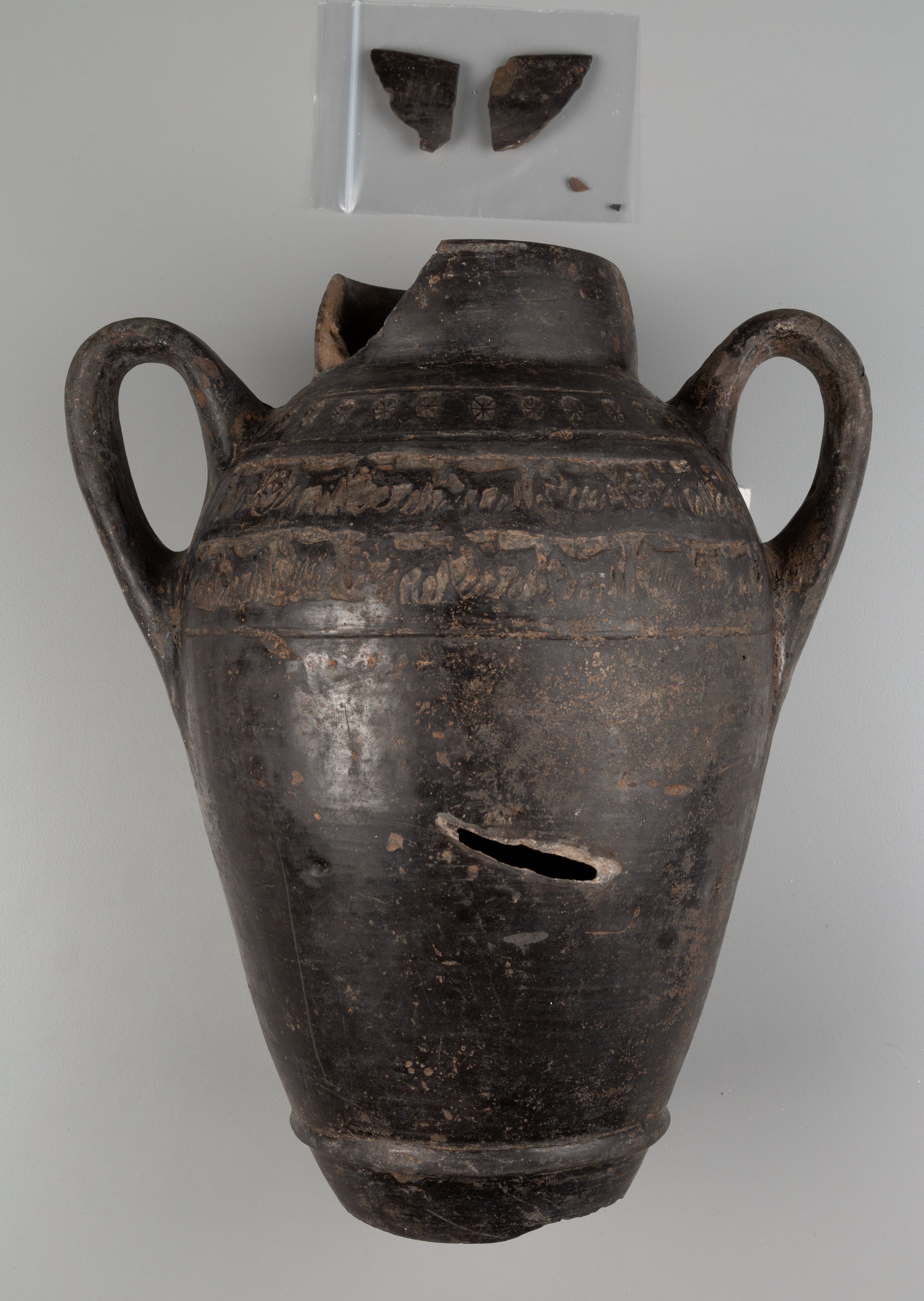 This photograph shows a shiny dark brown vessel with two curved handles, vertically oriented. There is a diagonal gash in the middle of the vessel. Above the vessel is a small plastic bag with four fragments inside; two are larger and two are very small.