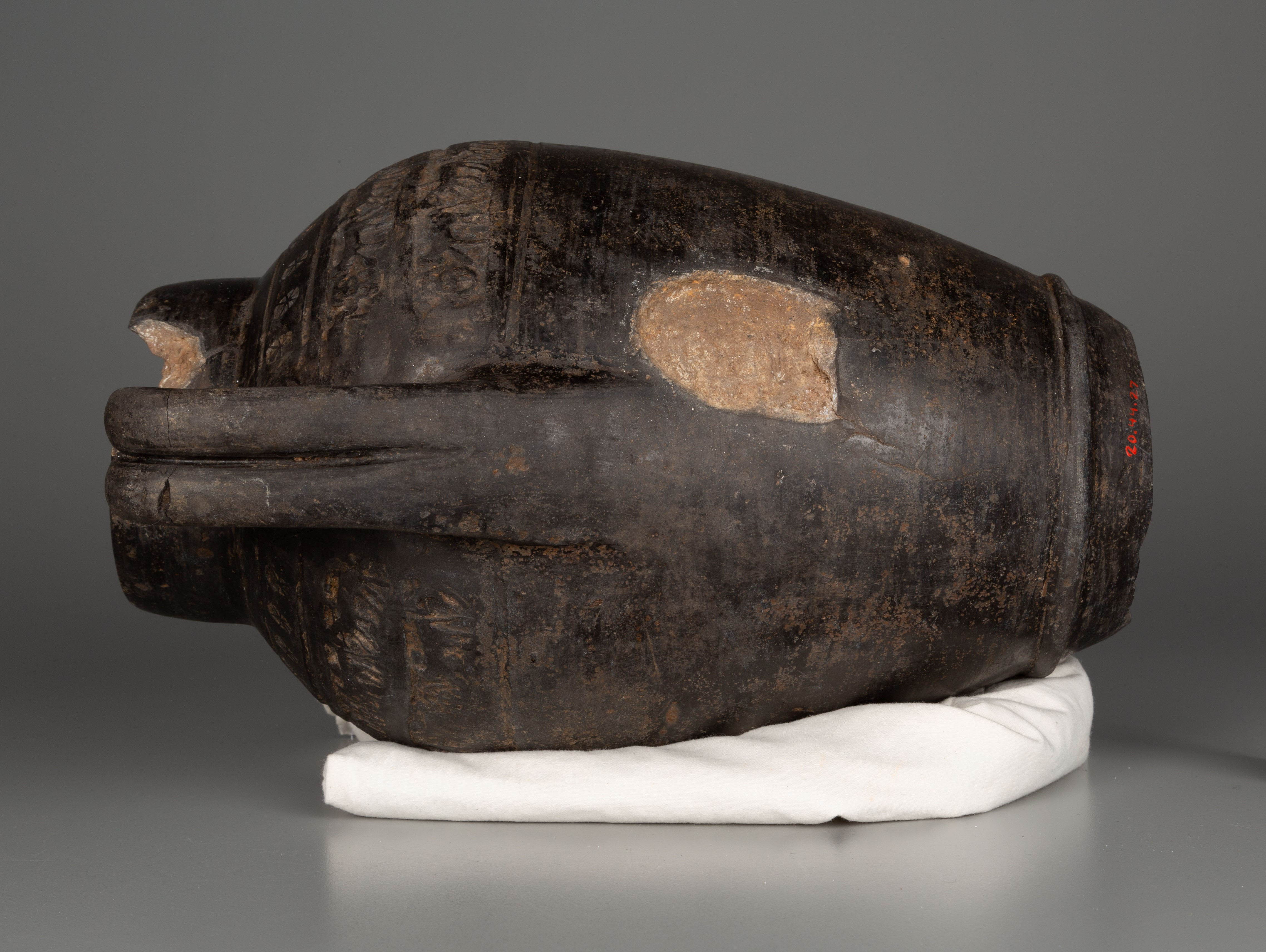 This photograph shows a dark brown-black vessel on its side, with one handle facing the viewer. It rests on a cream-colored cloth. A recessed patch on the body of the vessel is a lighter brown color.