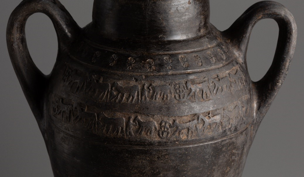 This close-up of a dark brown two-handled vessel shows two friezes impressed onto its surface. The friezes depict a repeating design consisting of five elements: a horse, a rider, a horse and foal, a person holding a horse by its bridle, and a geometric ornament. Lighter brown material is in the recessed areas of the friezes.