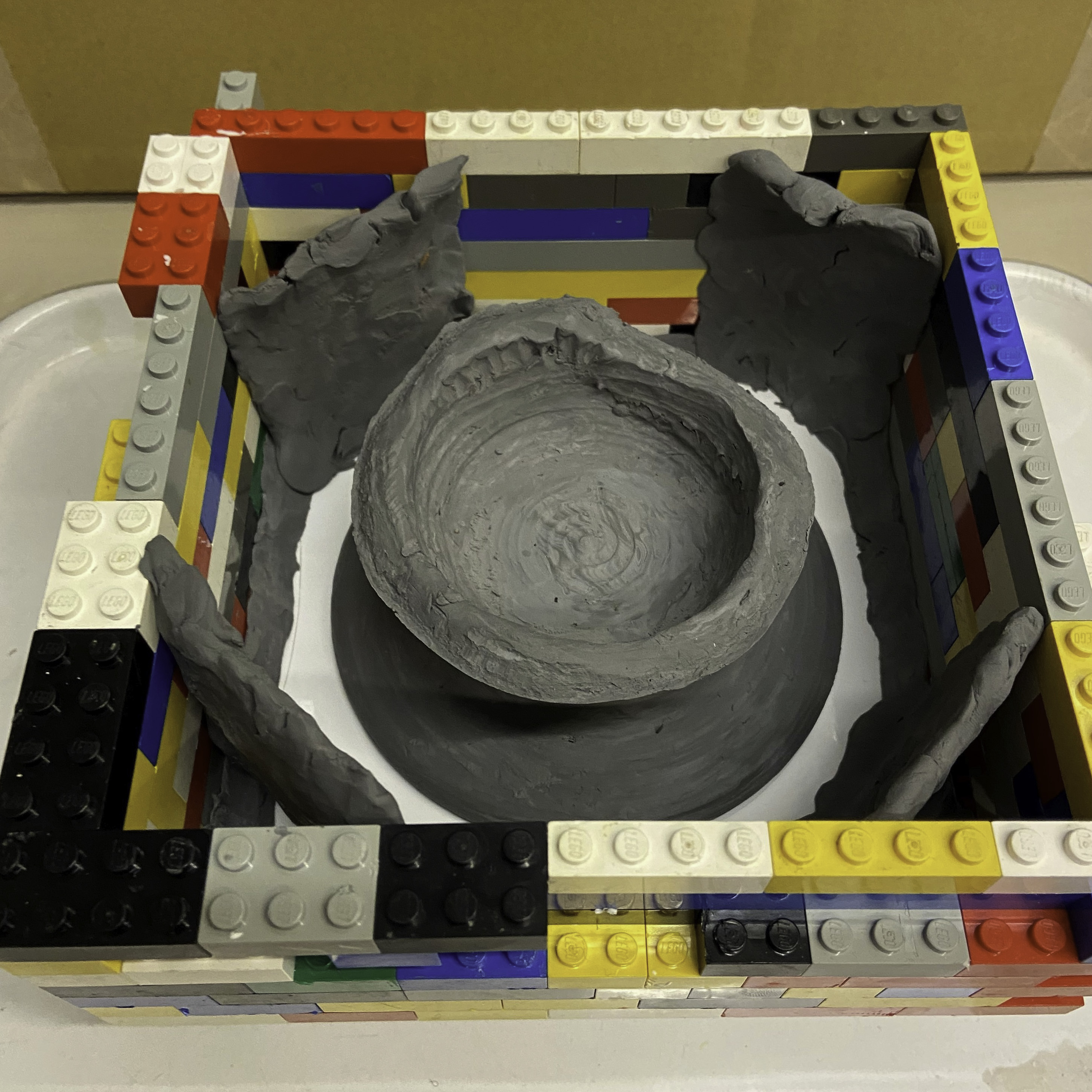 A gray clay base on a white tile is surrounded by walls of Legos and clay.
