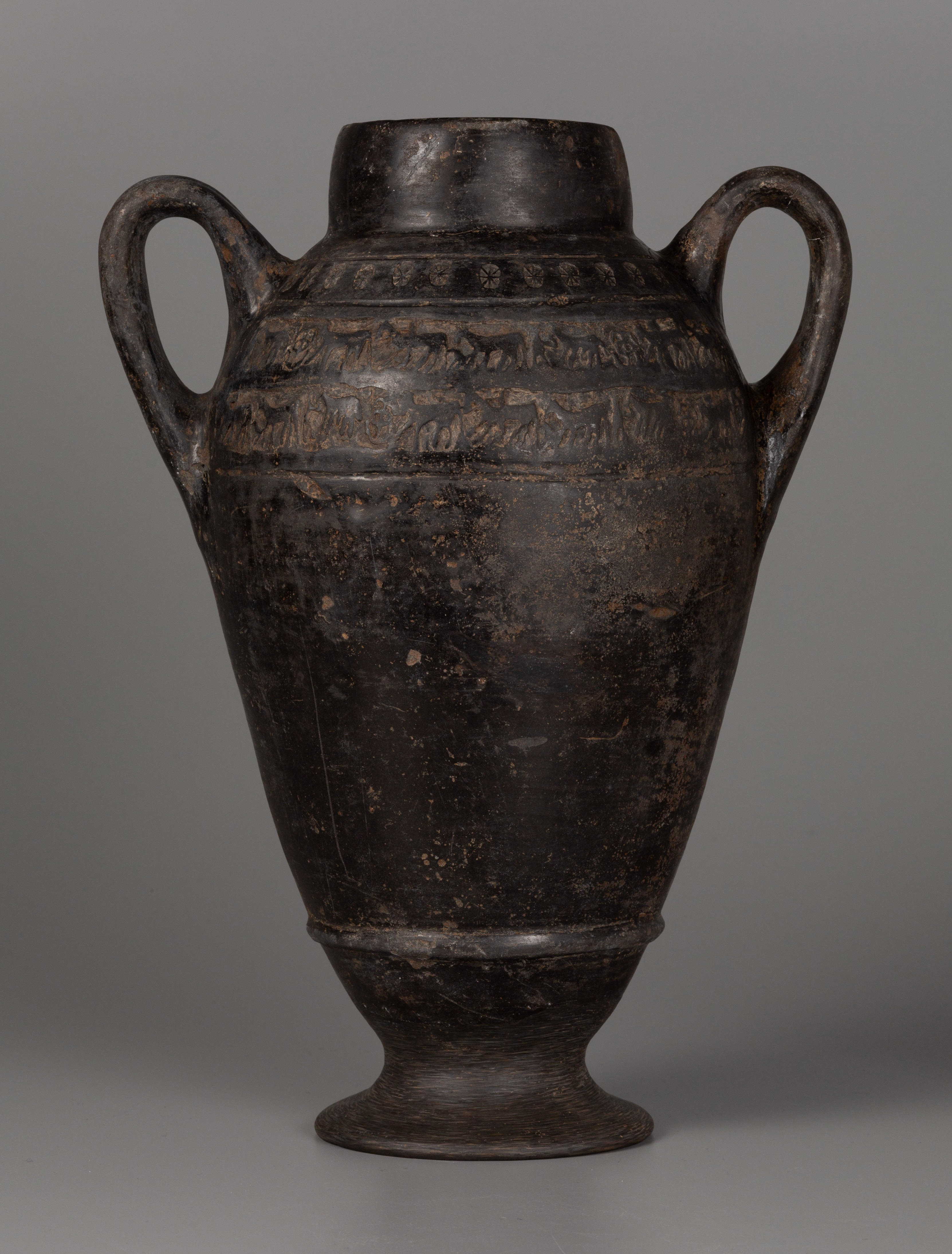 This photograph shows an amphora with a short cylindrical neck and two upward-curving handles attached at the shoulder. The body of the vessel tapers toward a flared foot. A raised ring encircles the body just above the foot. The shoulder zone displays impressed decoration: indvidual star patterns or rosettes above, and below two bands with figures of horses and riders. The surface of the amphora is nearly black and shiny; the base of the vessel has a slightly different surface finish.