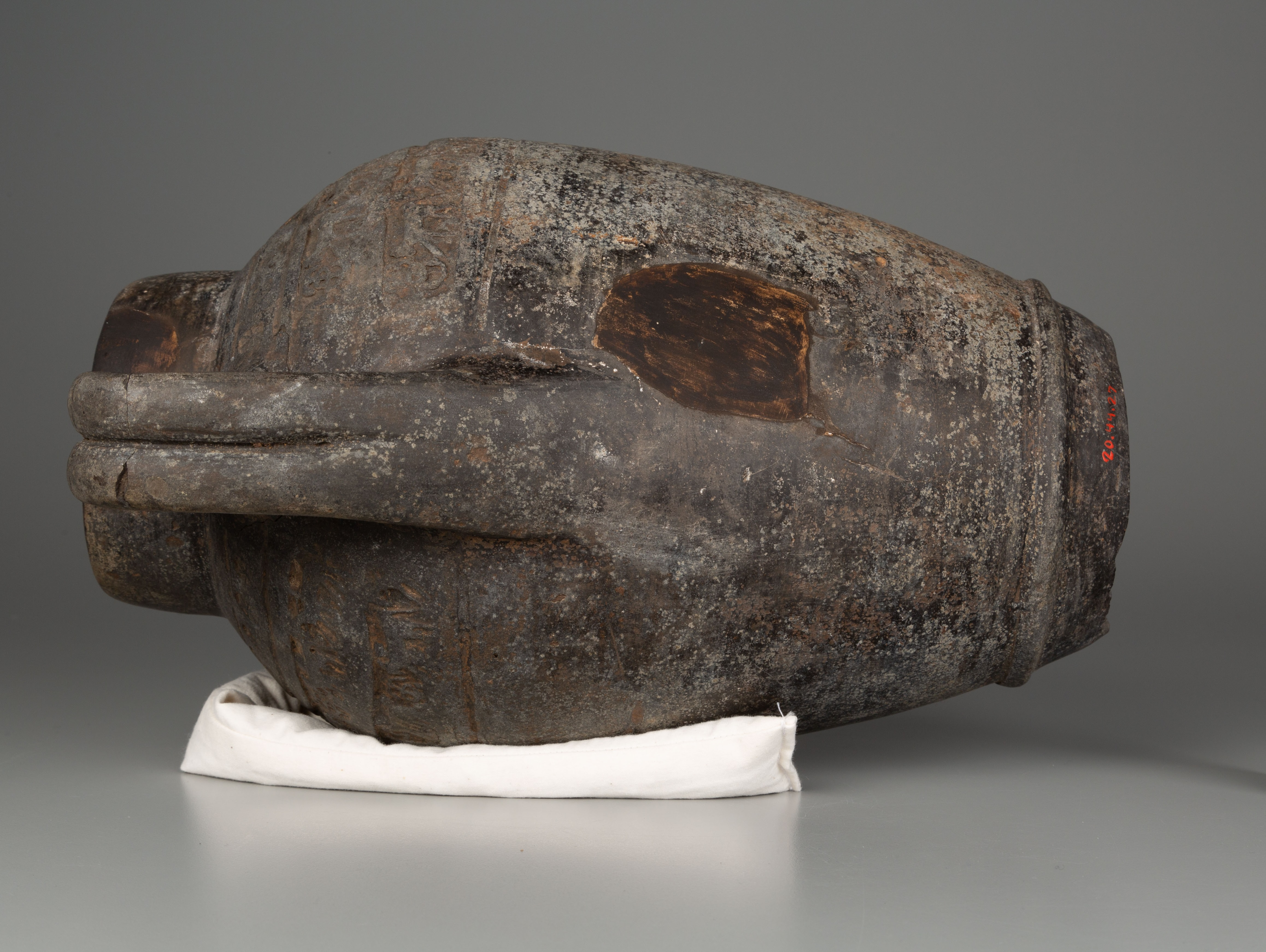 This photograph shows a worn brown vessel with a missing base. It is lying on its side, with one of the handles facing the viewer, and is placed on a cream-colored cloth. There are pale surface encrustations and one dark patch just above the handle.