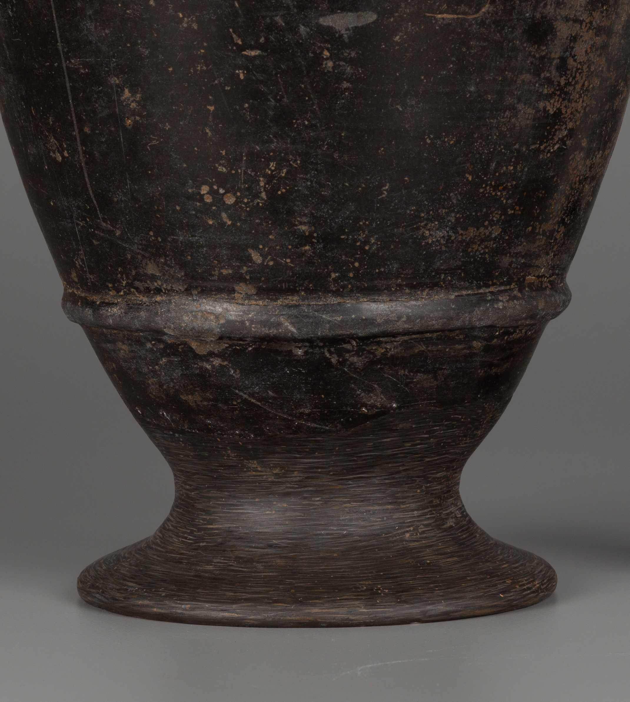 This photograph shows the lower portion of a vessel. The base is covered in short horizontal paint strokes, distinguishing it from the uniform dark brown-black ceramic above.