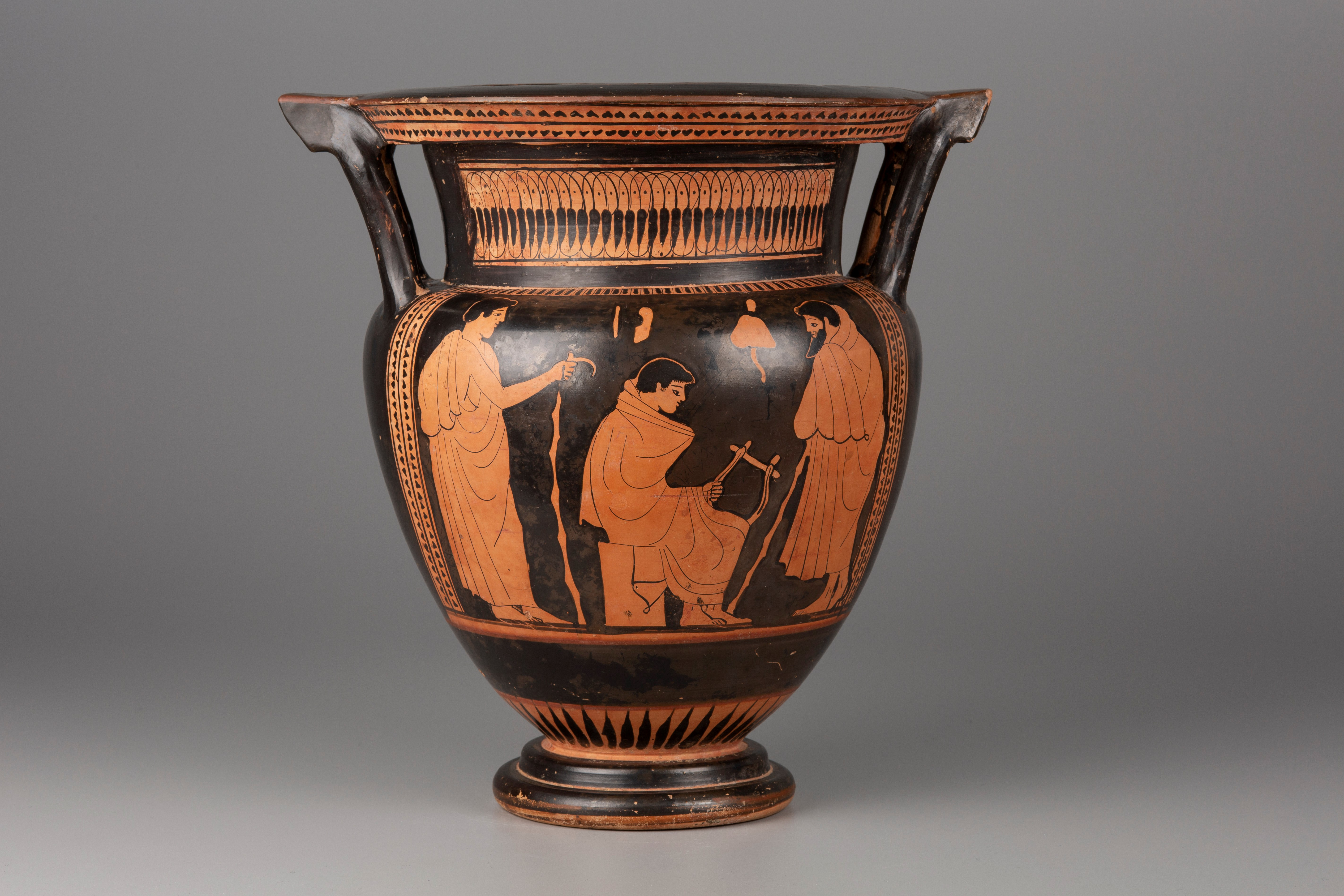 A color photograph shows a wide-mouthed jar with a flaring base. On each side, a handle connects the vessel's shoulder to its projecting rim. On the belly of the jar are orange figures set against a black ground. At the center, a seated boy enveloped in a mantle holds a lyre. He is framed by two men with walking sticks. One is bearded, the other is not; both are draped with copious cloaks. Athletic implements, including jumping weights, a sponge, and a strigil, are suspended above the boy.