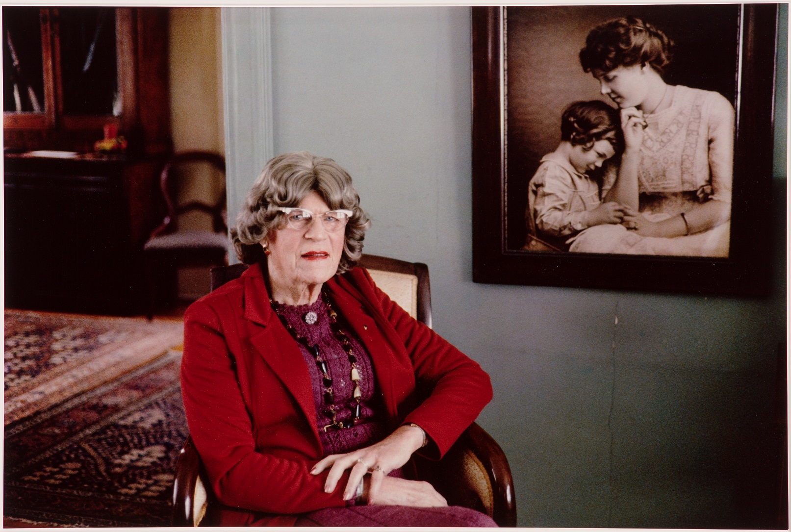 An elderly trans woman is shown in a home furnished with antiques and patterned rugs. She is looking straight at the camera. Dressed in a red jacket and blouse, and adorned with a long necklace, she sits in an upholstered chair in front of a large framed black and white photograph. The photograph shows a seated mother turning to a standing young child who is resting her head on her shoulder.
