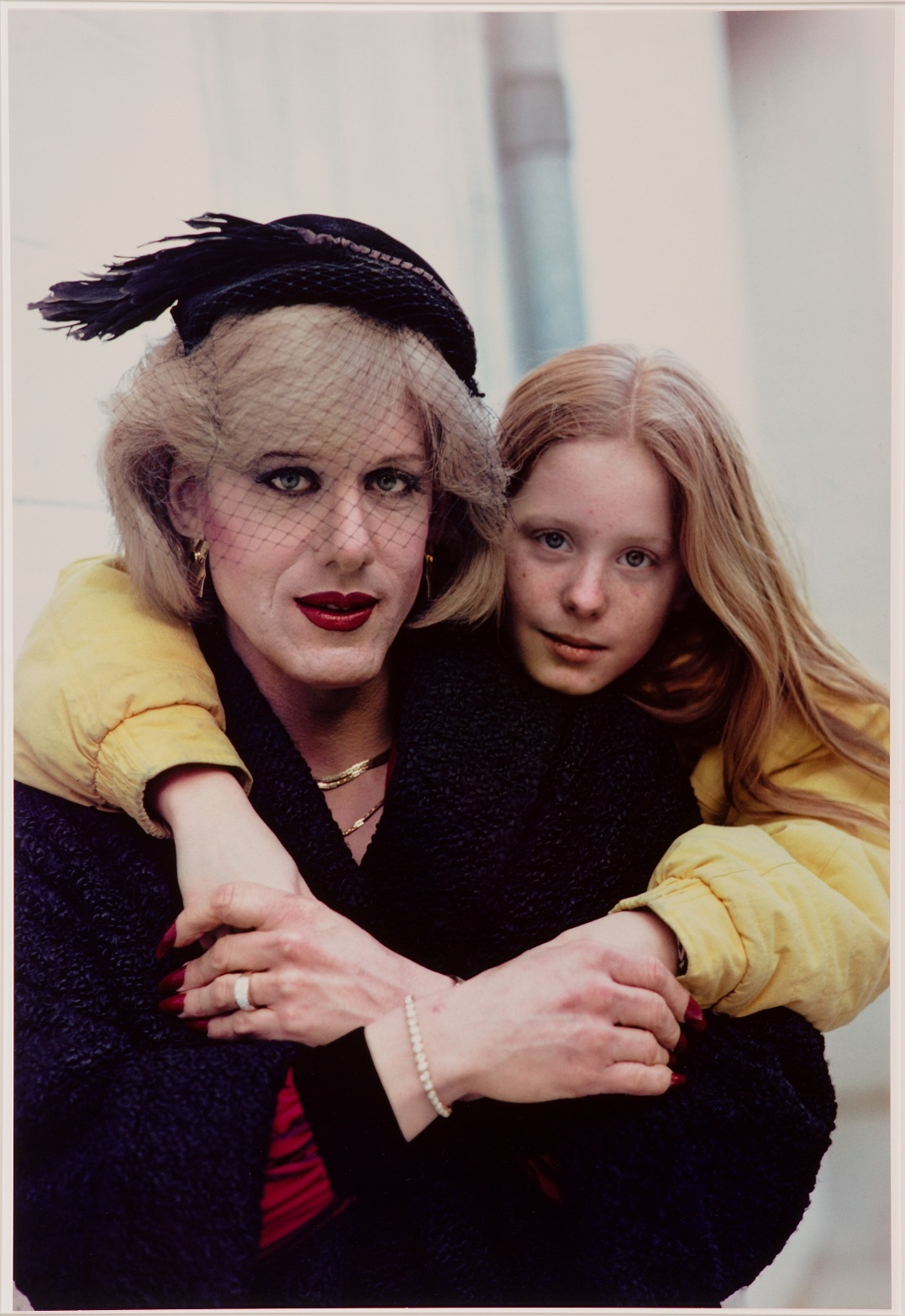 A trans woman in a black jacket and hat crosses her hands in front of her chest. She holds the hands of a girl dressed in yellow who leans over her from behind, her chin propped on the woman's proper left shoulder. The girl has long reddish-blond hair parted in the middle; the woman's hair is light blond and shorter. She wears jewelry, dark eyeliner, dark red lipstick, and her fingernails are painted dark red. The hat has a black feather and a short netted veil attached to it.