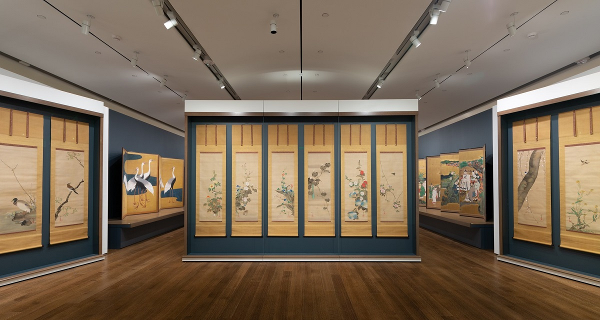 This photograph shows 10 painted scrolls hanging behind glass in a gallery with navy blue walls and brown hardwood floors. There are two scrolls hanging together on the left and right sides of the photograph and 6 scrolls hanging together in the middle. Each scroll features different birds and flowering plants. The paintings have identical golden yellow matting and two ties at the top. In the background, you can see two additional folding screenings being displayed on raised platforms in an adjacent space.